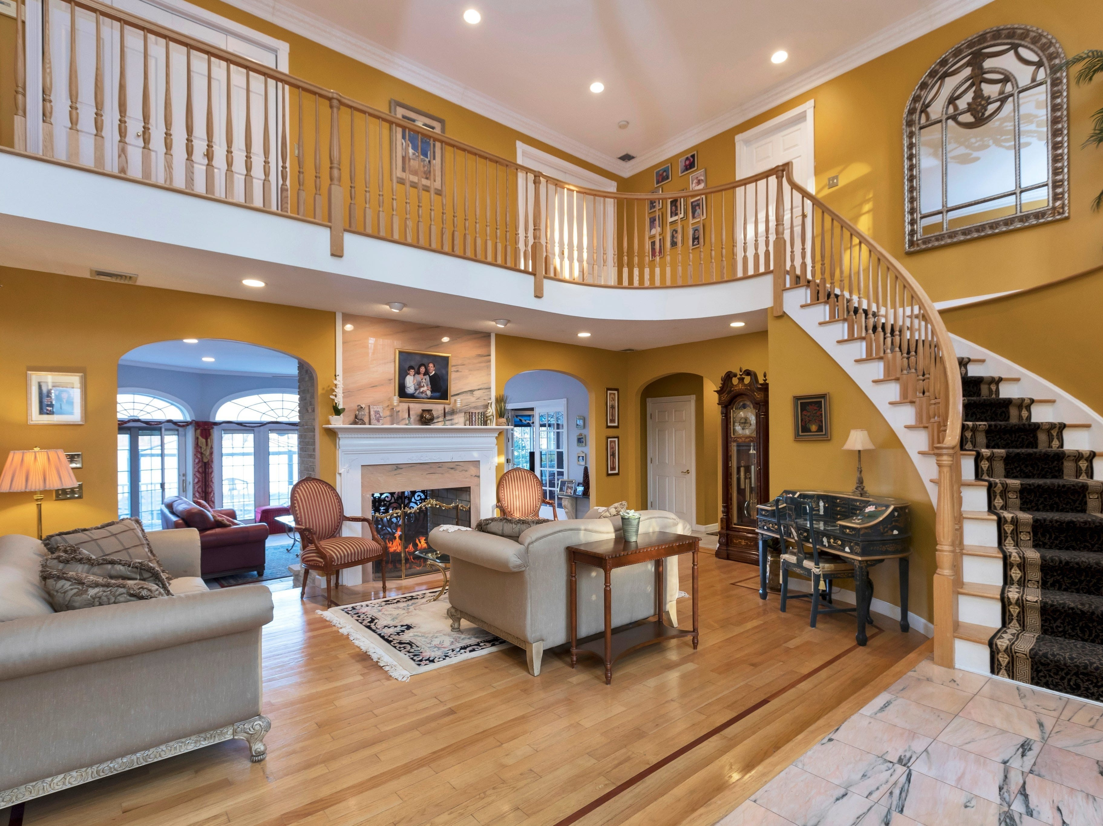 The home's open floor plan presents visitors with lake views visible through the arching windows and doors of the family room behind the two-story great room.