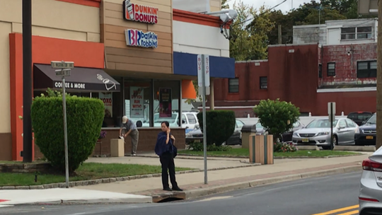 A woman waits near a bus stop to cross busy South Washington Avenue mid-block in Bergenfield at the spot where Robert Armbruster was fatally injured.