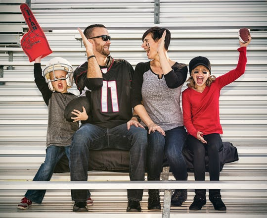 A family of four cheers on their favorite football team while sitting in the bleachers.