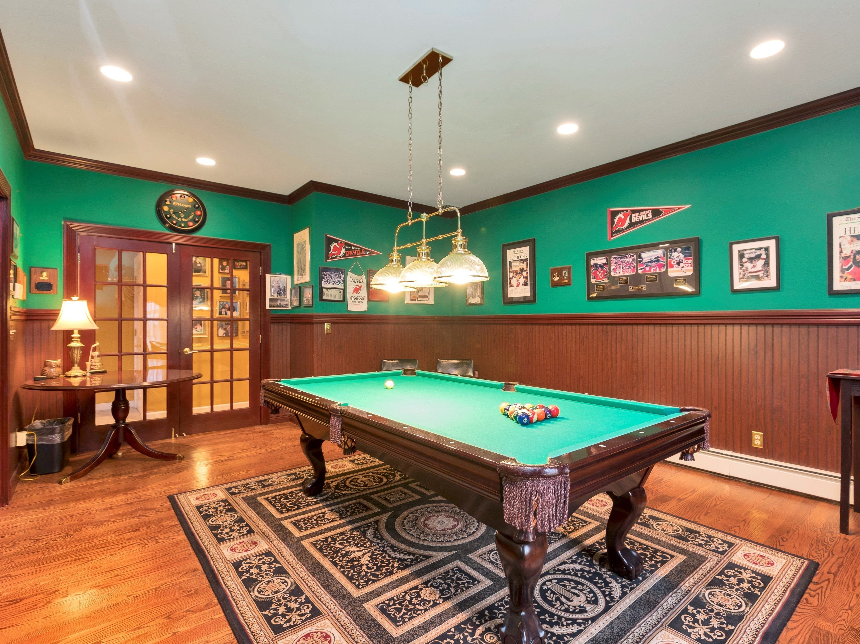The billiard room is on the first floor rather than the basement, making it more accessible; the wainscoting and chair rail add warmth to the large room.