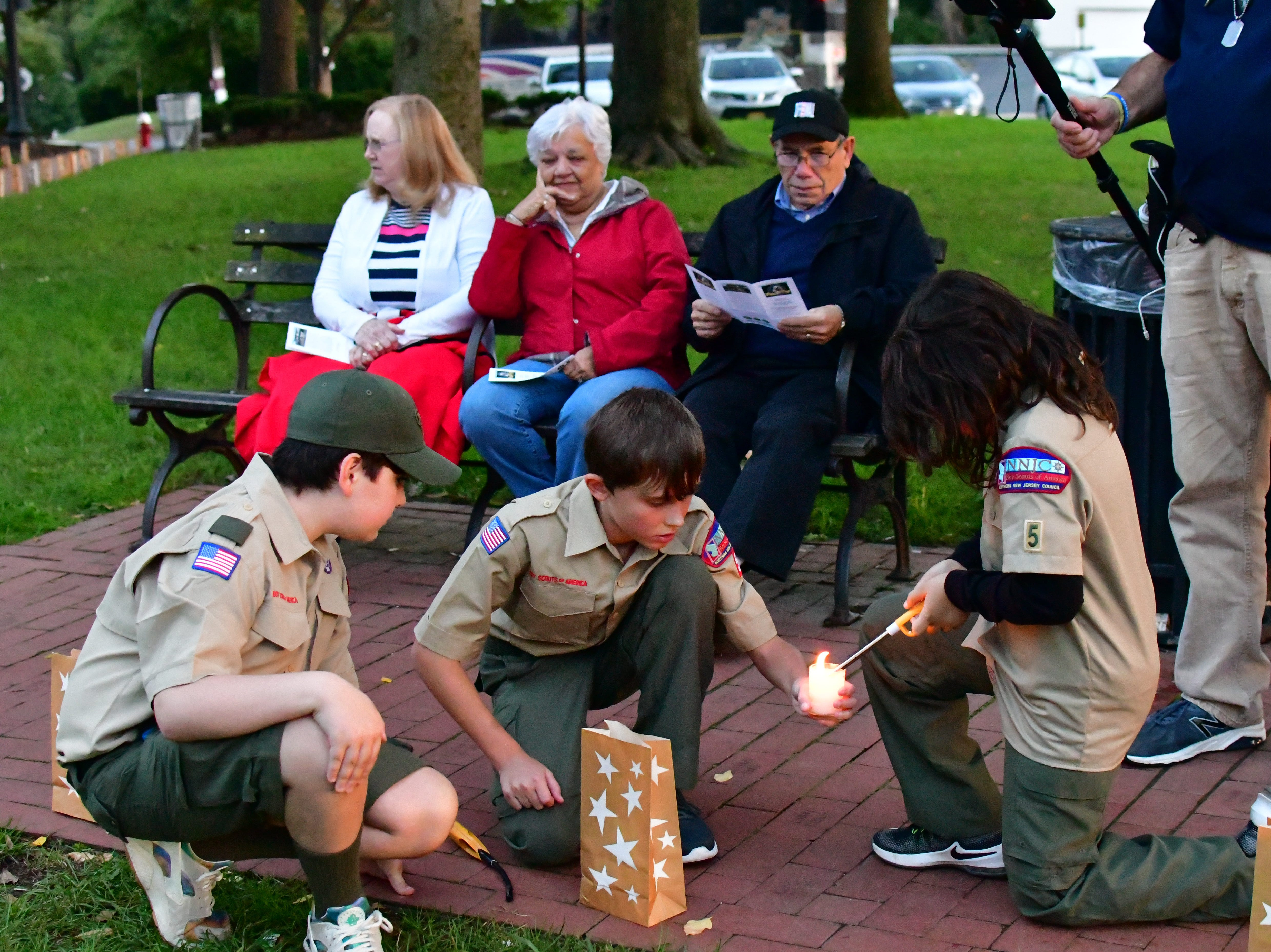 Helping light the luminaries, are boy scouts Joshua Harrold, Adam Mannina, John Cauagnuolo (shown in any order).  The Gold Star Mother's Day Committee sponsored its eighth annual event commemorating Gold Star Mother's Day on Sept. 30, at Van Neste Park, Ridgewood. After a short ceremony, hundreds of luminaries were lit to honor Gold Star Mothers (moms who had lost sons and daughters to the war) and their families.
