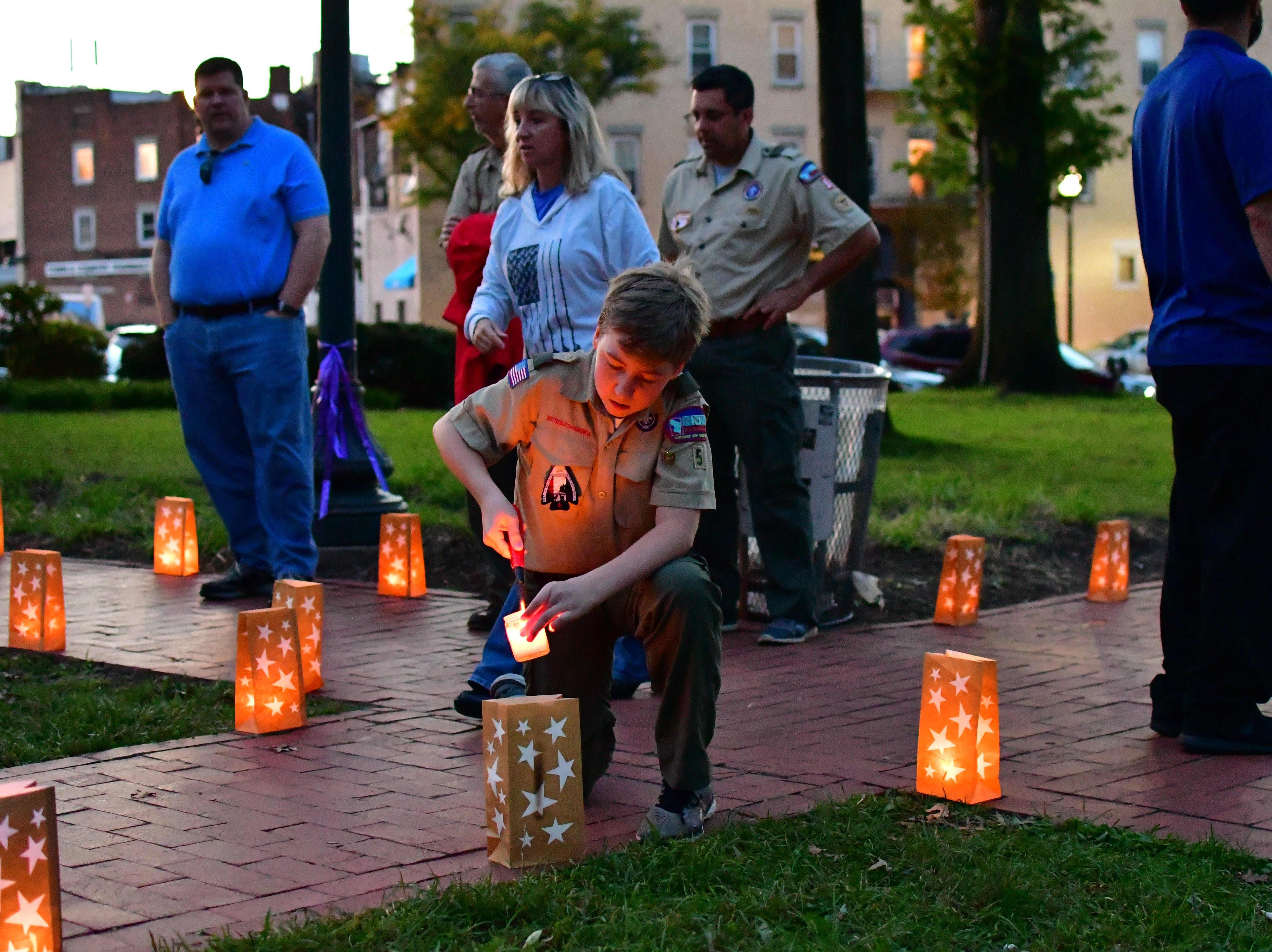 Spencer Stephens lights a luminary before the ceremony. The Gold Star Mother's Day Committee sponsored its eighth annual event commemorating Gold Star Mother's Day on Sept. 30, at Van Neste Park, Ridgewood. After a short ceremony, hundreds of luminaries were lit to honor Gold Star Mothers (moms who had lost sons and daughters to the war) and their families.