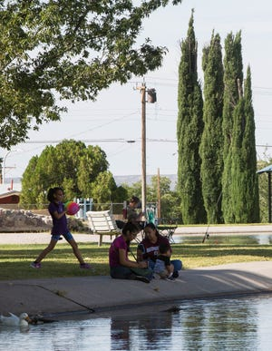 Diana Gaytan, right, with Felipe Martinez, 1, center, his mom Rebecca Martinez, left, and Melanie Gaytan , 8, hang out at Young Park. One of the Las Cruces City Parks that has been helped by the Land and Water Conservation Fund, Monday October 1, 2018.