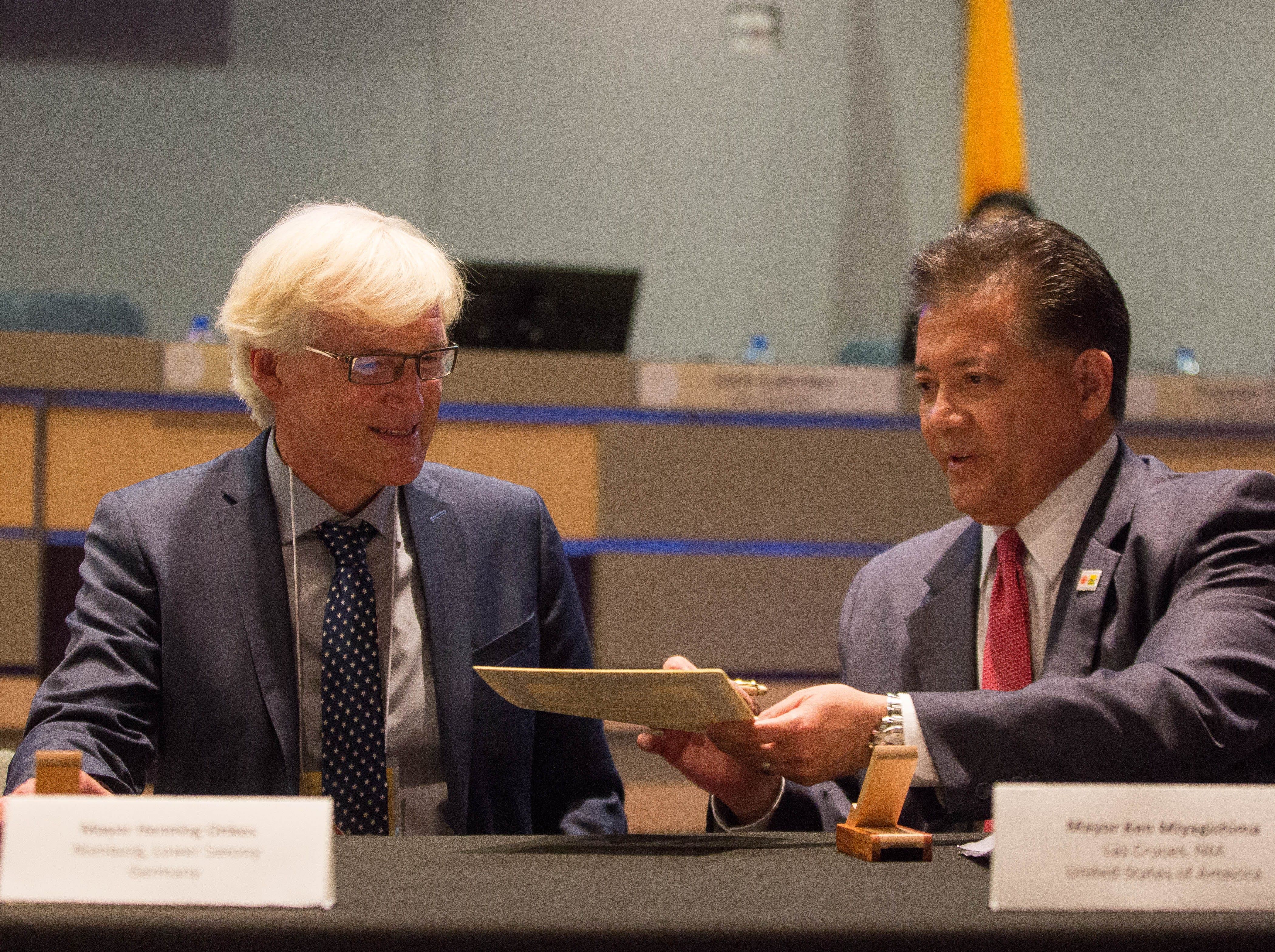 Ken Miyagishima, mayor of Las Cruces, hands signed documents to Henning Onkes, the mayor of Nienburg, Germany.  The city of Las Cruces and representatives of Las Cruces' sister city Nienburg  Germany re affirmed the sister cities status, Monday, October 1, 2018, before the city council meeting at the Las Cruces City Council Chambers.