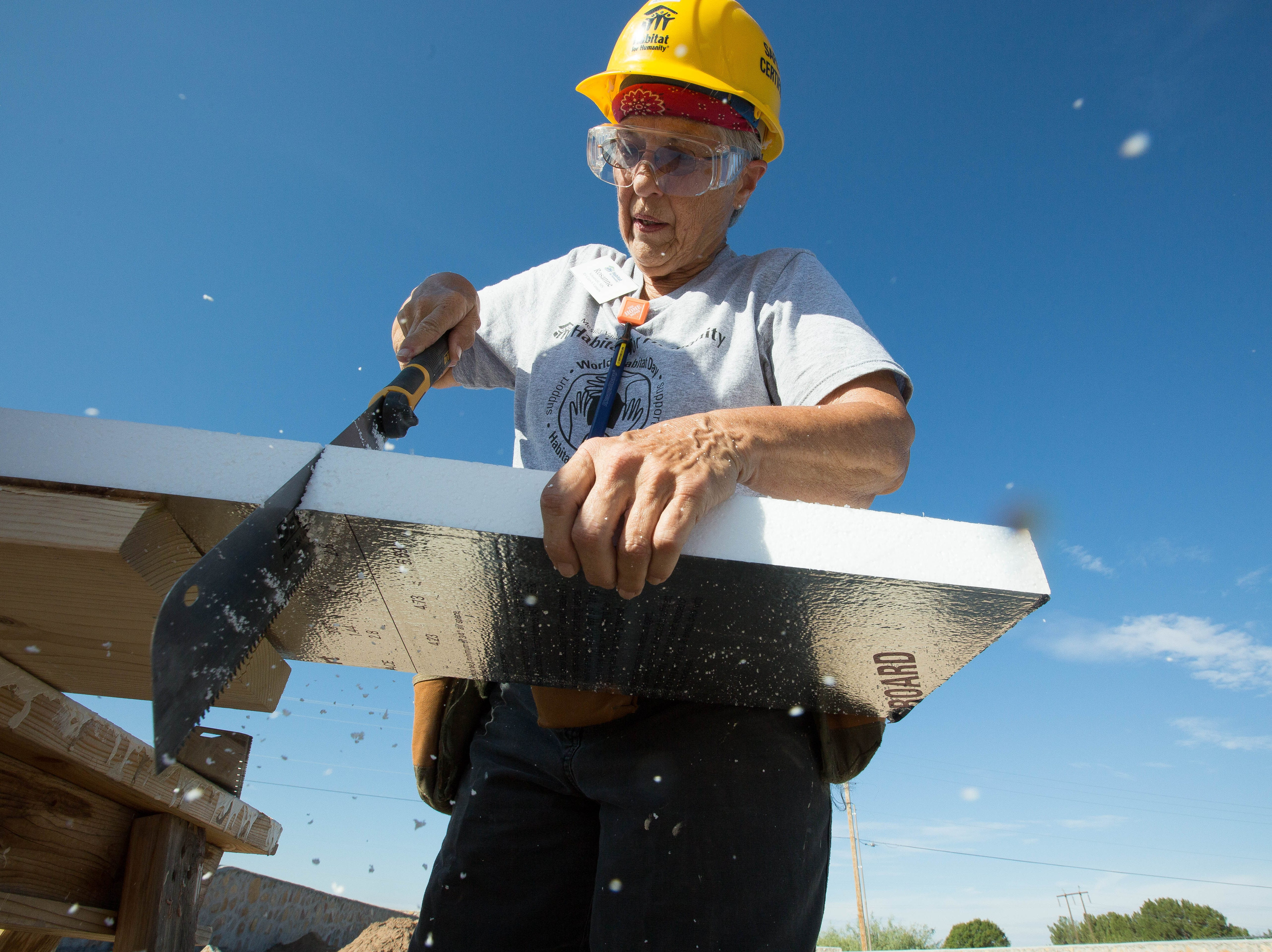 Roseanne Schoemehl, cuts insulation for the headers around window at the Habitat for Humanity build site on Aurora Star Court, Monday October 1, 2018.