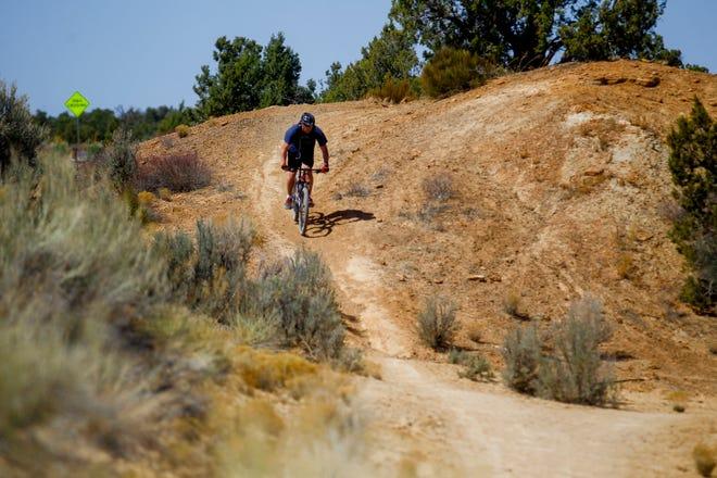 Jon Lillywhite rides his bike, Thursday, April 26, 2018 along the Anasazi Trail in Farmington.