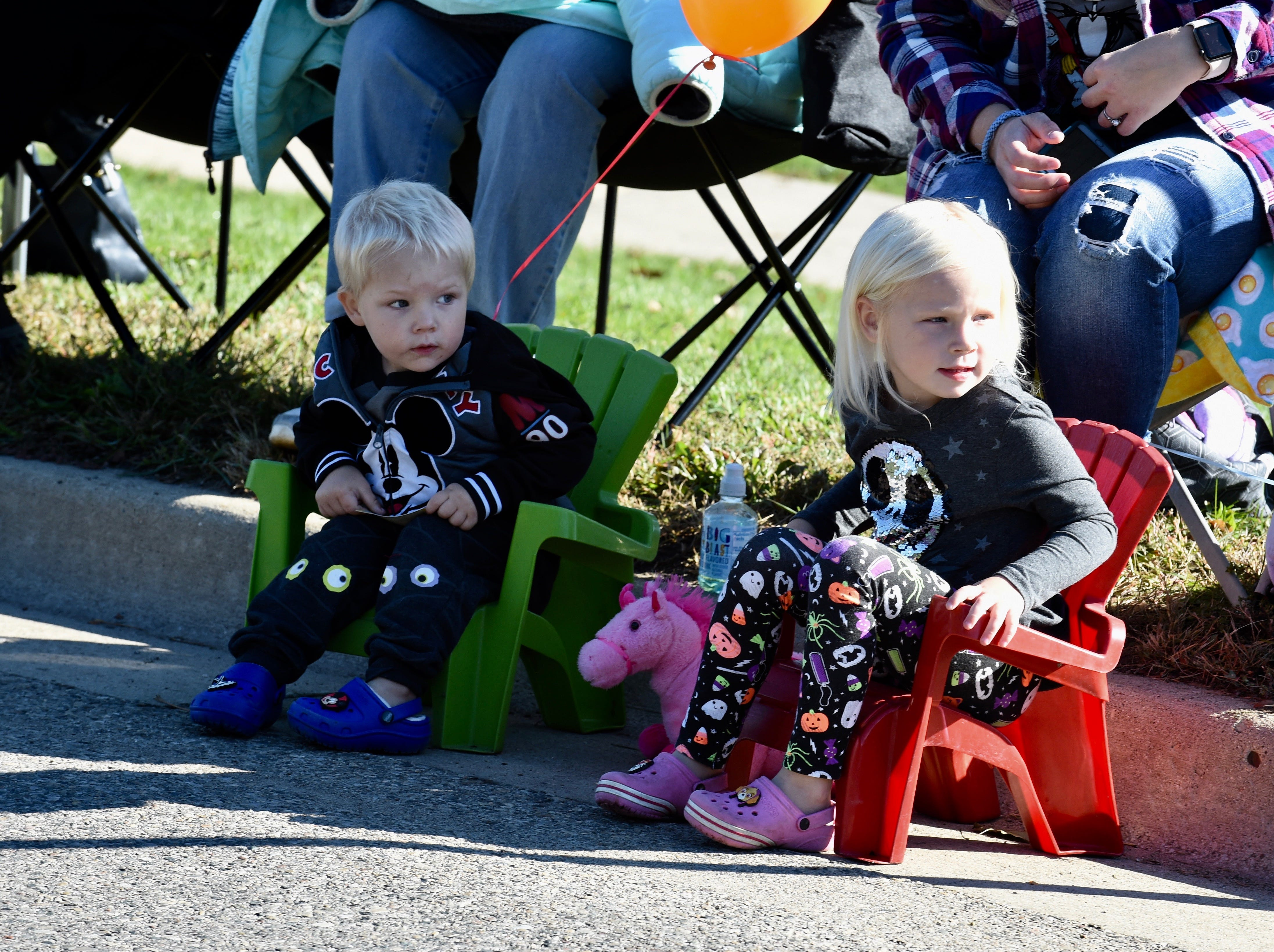 Myles and Elliza Visser look as the Pumpkin Parade makes its way down Pontiac Trail Saturday morning in South Lyon.