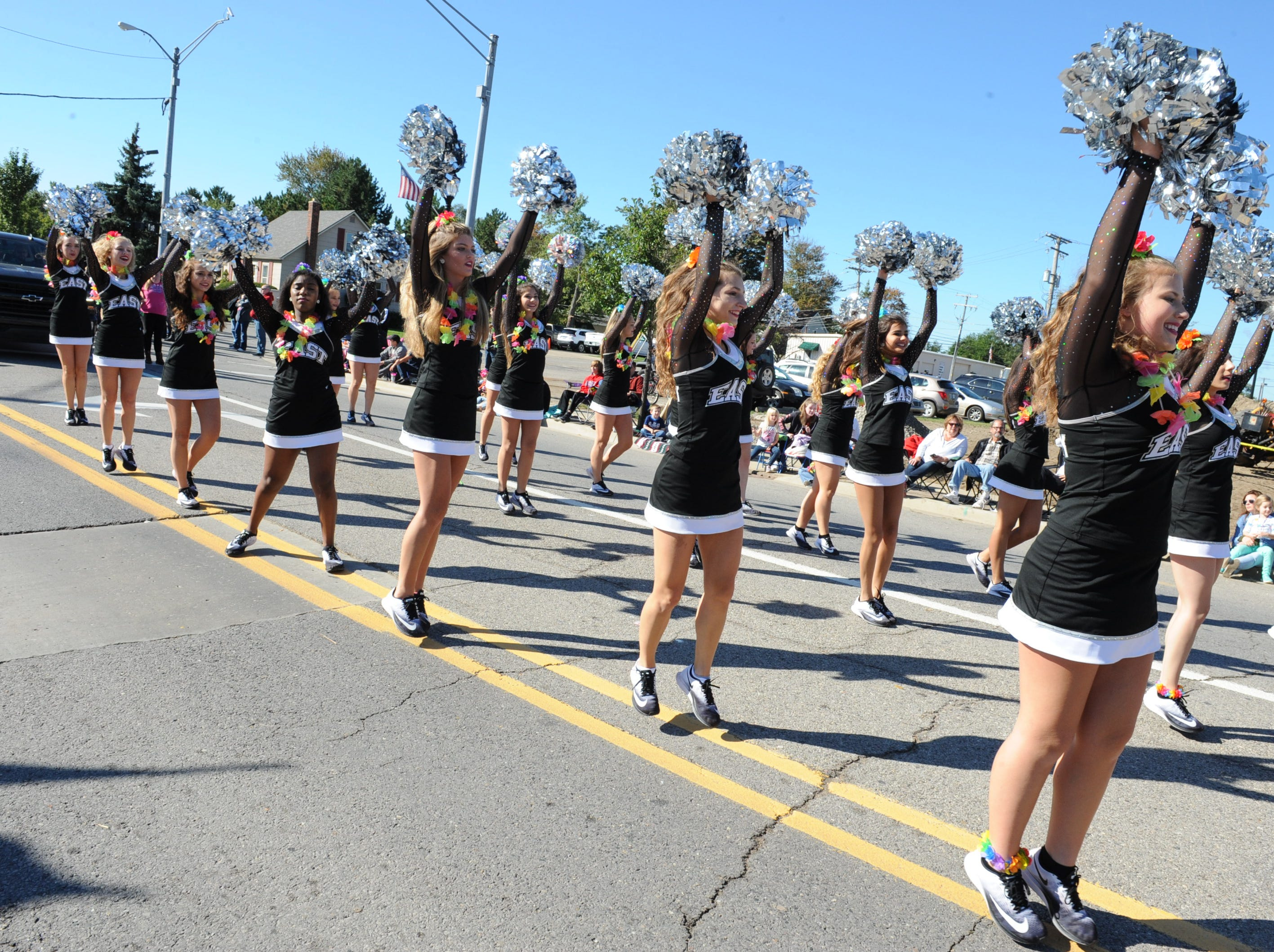 The South Lyon East High School varsity pom team takes part in the Pumpkin Parade held Saturday.