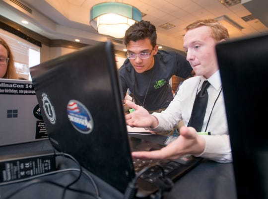 UWF students Justin Fruitticher, left, and John Chambler work during ITEN Wired Cyber Competition at the Hilton in Pensacola Beach on Monday, October 1, 2018.