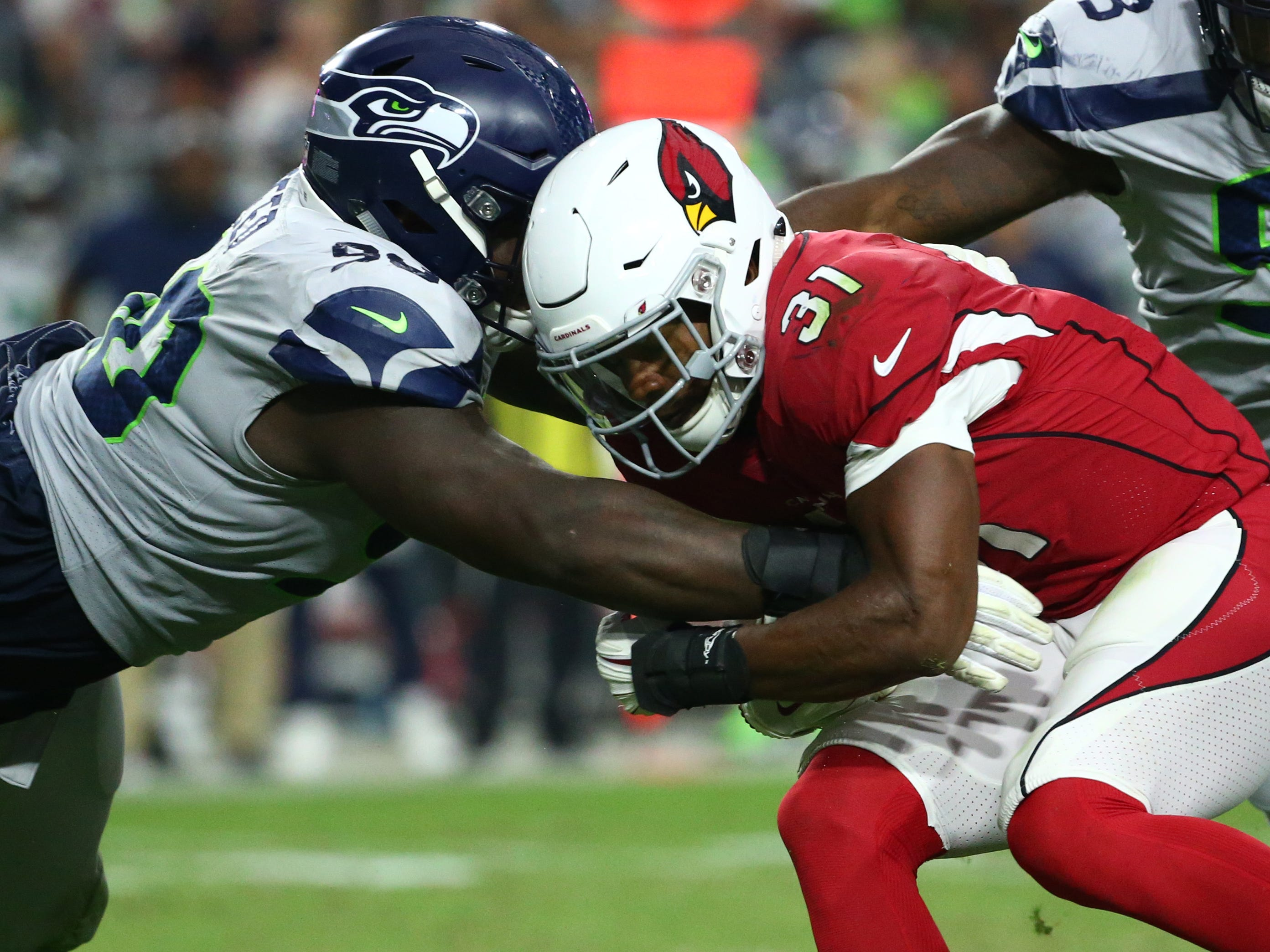 Arizona Cardinals David Johnson is tackled by Seattle Seahawks Jarran Reed in the second half at State Farm Stadium in Glendale, Ariz.