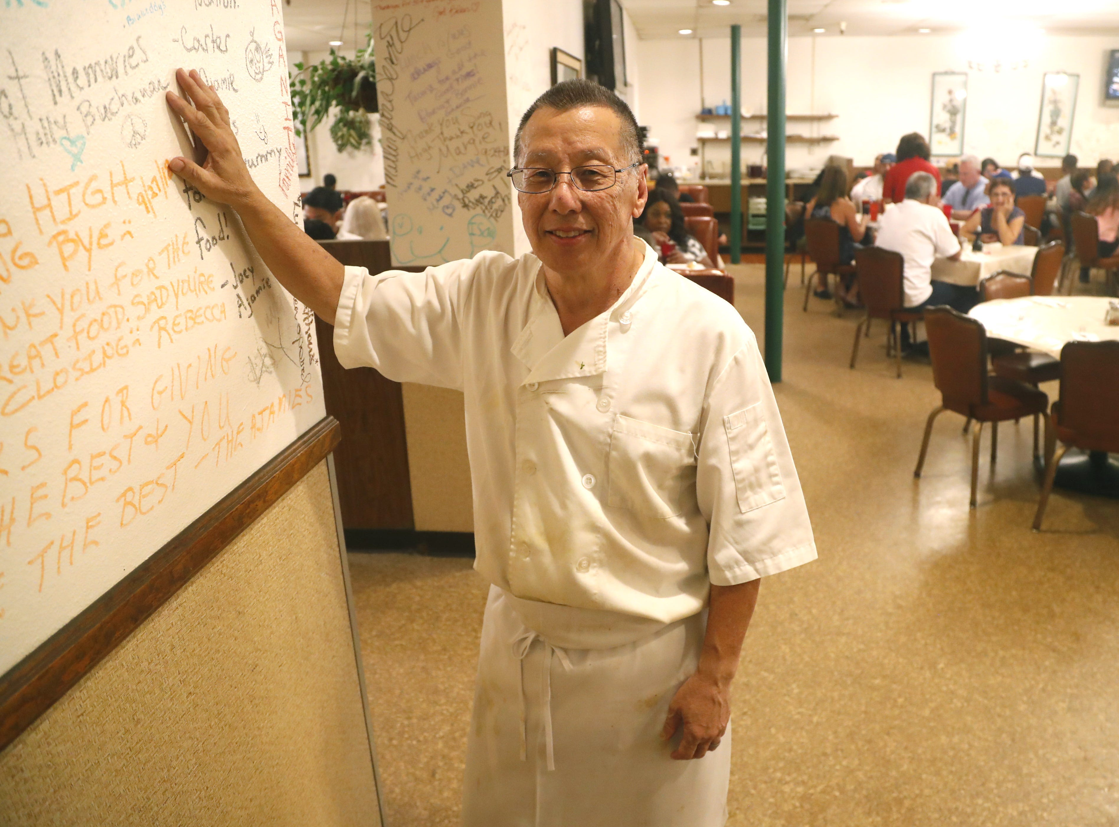 Owner Harlan Lee places his hands on some of the words written by customers at Sing High Chop Suey House's last day in downtown Phoenix.
