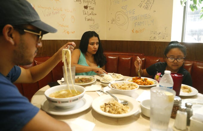 Adrian Hernandez (from left to right), Gail Raganit and Justice Robinson eat some of the Cantonese-American cuisine on Sing High Chop Suey House's final day in downtown Phoenix on Sept. 30, 2018.