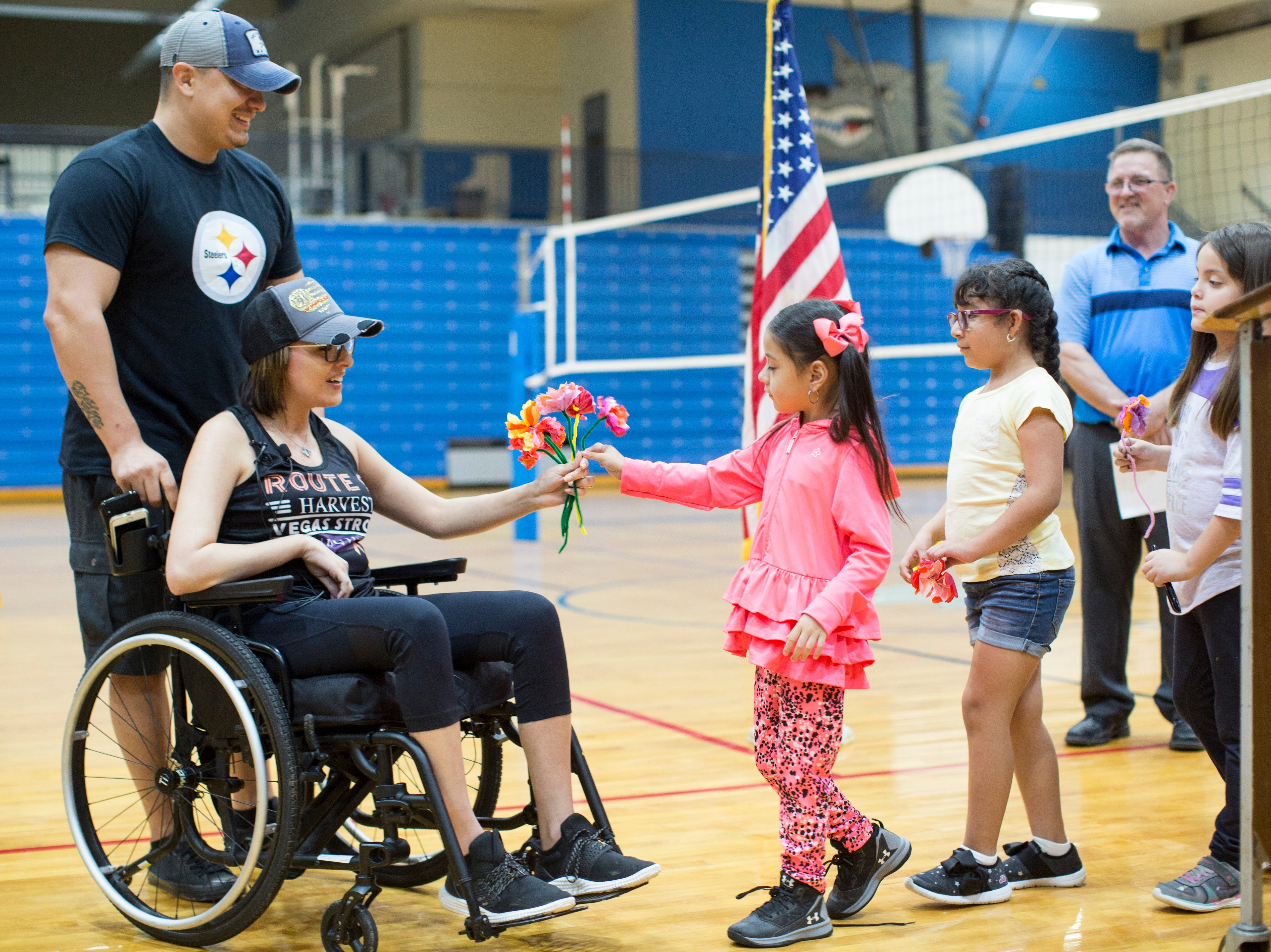 Alexia Perez gives Jovanna Calzadillas a flower during a school assembly at Hayden High School in Winkleman to honor her courage recovering from a severe gunshot wound during the Route 91 Harvest Festival mass shooting.