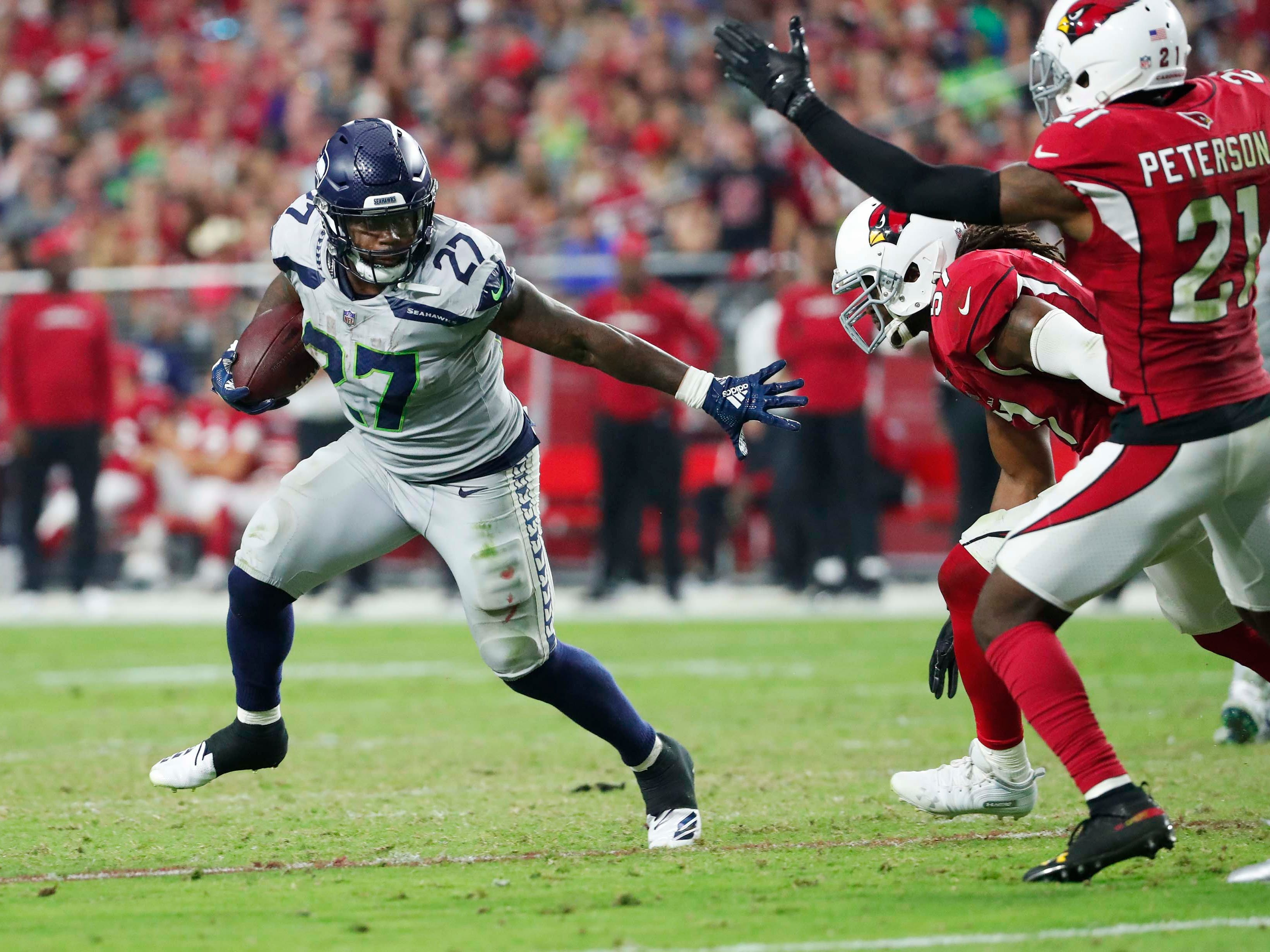 Seattle Seahawks running back Mike Davis (27) runs against Arizona Cardinals linebacker Josh Bynes (57) and defensive back Patrick Peterson (21) during the third quarter at State Farm Stadium in Glendale, Ariz. September 30, 2018.