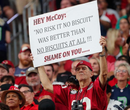 An Arizona Cardinals fan holds a sign directed at Arizona Cardinals offensive coordinator Mike McCoy during the first quarter against the Seattle Seahawks at State Farm Stadium in Glendale, Ariz. September 30, 2018.