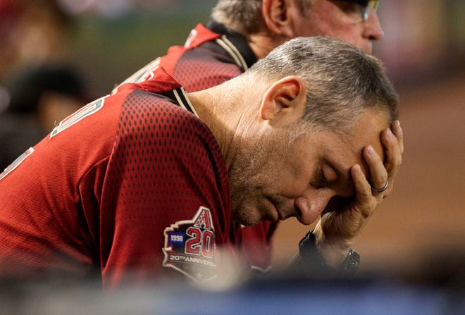 FILE - In this Sept. 23, 2018, file photo, Arizona Diamondbacks manager Torey Lovullo wipes his brow during a baseball game against the Colorado Rockies, in Phoenix. The Diamondbacks were in contention for a second straight playoff appearance late into the season. A late collapse knocked them out of the race and may have put them at a crossroads.