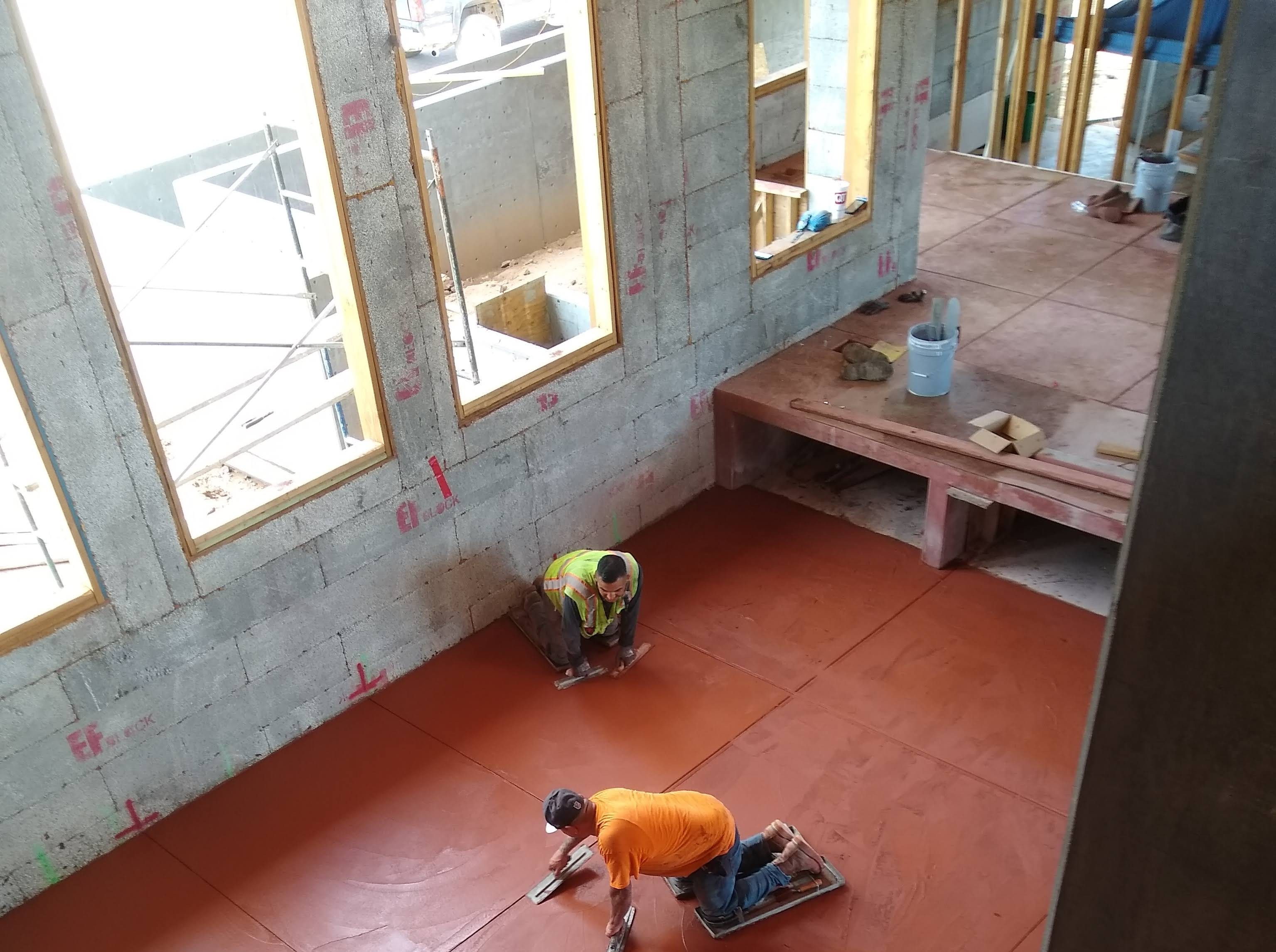 The family room, on the opposite side of the fireplace, is located to the front of the house. Tall windows above eye level soften boundaries between the interior and exterior of the house while providing privacy. The red concrete floors will be waxed and polished.