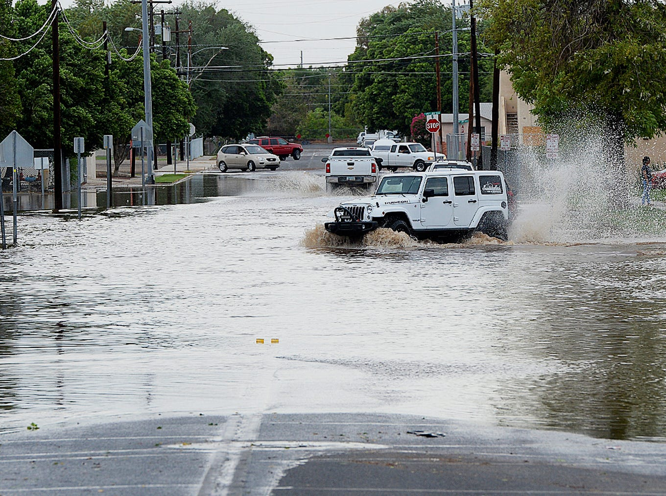 Vehicles navigate a flooded 5th Street in Yuma, on Sept. 30, 2018, after an early afternoon rain storm.