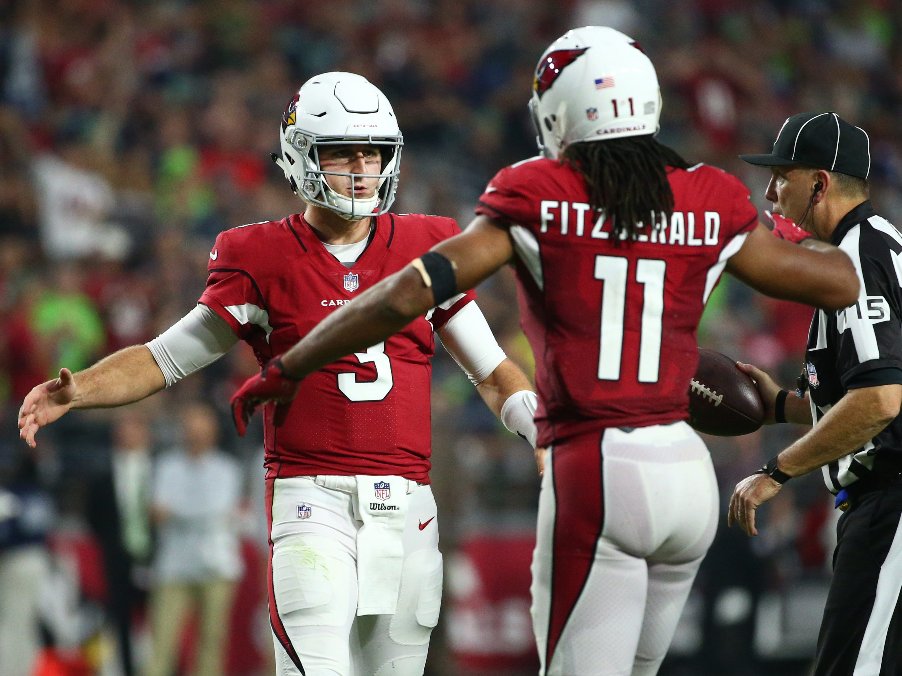 Arizona Cardinals quarterback Josh Rosin and Larry Fitzgerald react after a pass completion against the Seattle Seahawks in the first half at State Farm Stadium in Glendale, Ariz.