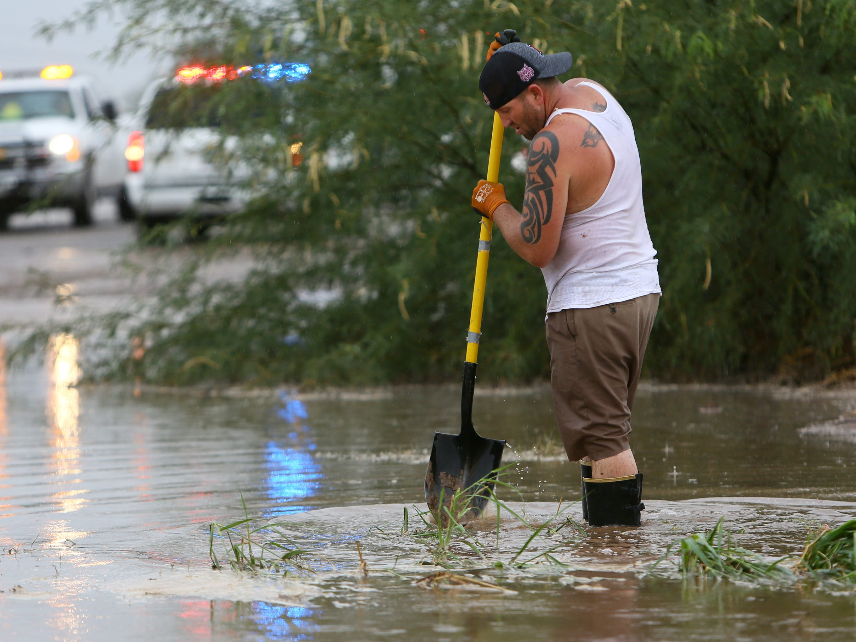 A Tucson resident who said his backyard was flooded tries to dislodge debris from a wash behind homes at North Cerius Stravenue and West Calle Maverick during rain from the remnants of Hurricane Rosa in Tucson on Oct. 1, 2018.