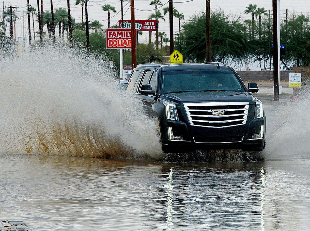 A vehicle drives east on a flooded street following a rain storm, in Yuma on Sept. 30, 2018.