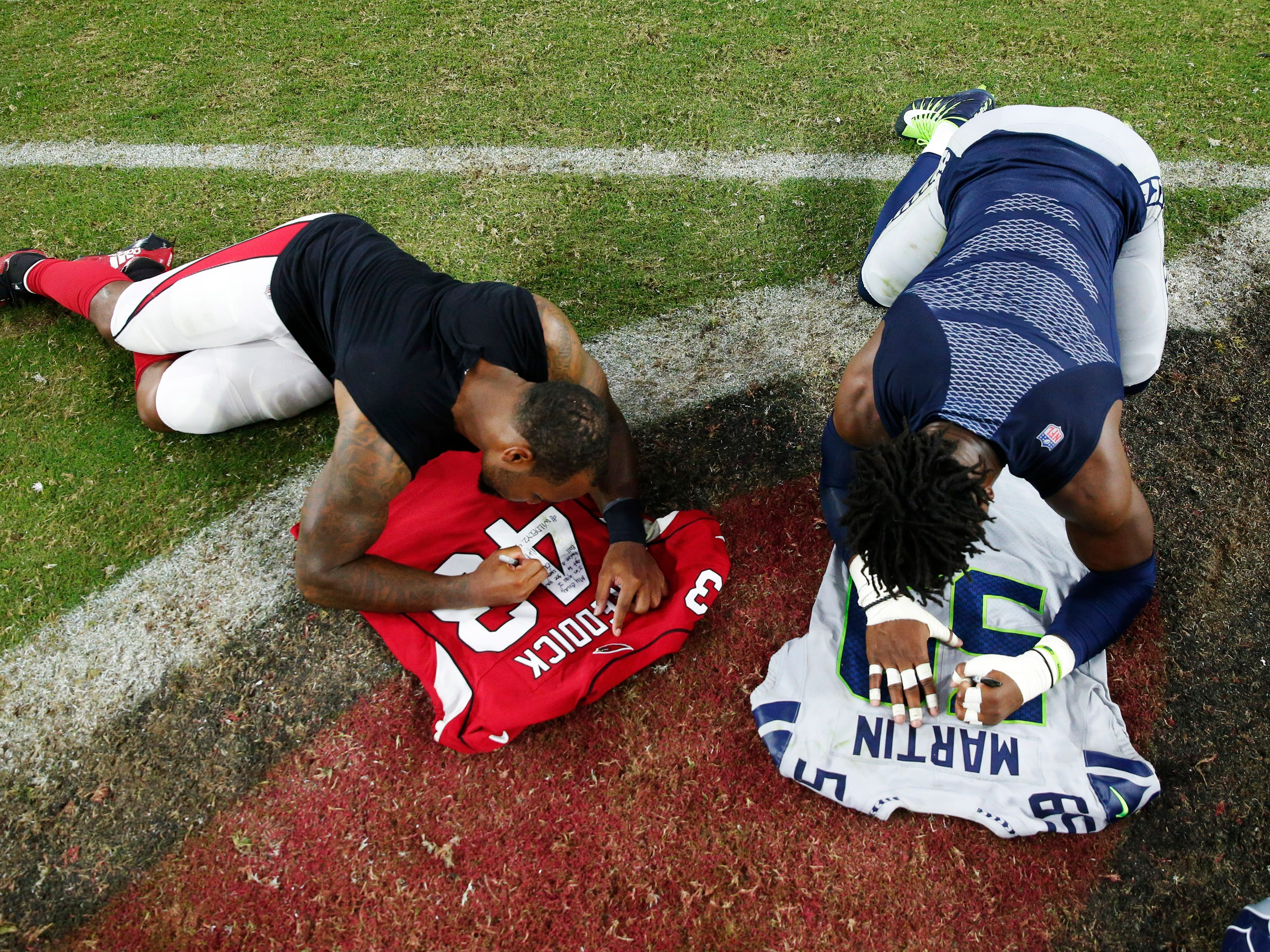 Arizona Cardinals linebacker Haason Reddick (43) and Seattle Seahawks linebacker Jake Martin (59) exchange jerseys after the Seattle Seahawks won 20-17 at State Farm Stadium in Glendale, Ariz. September 30, 2018.