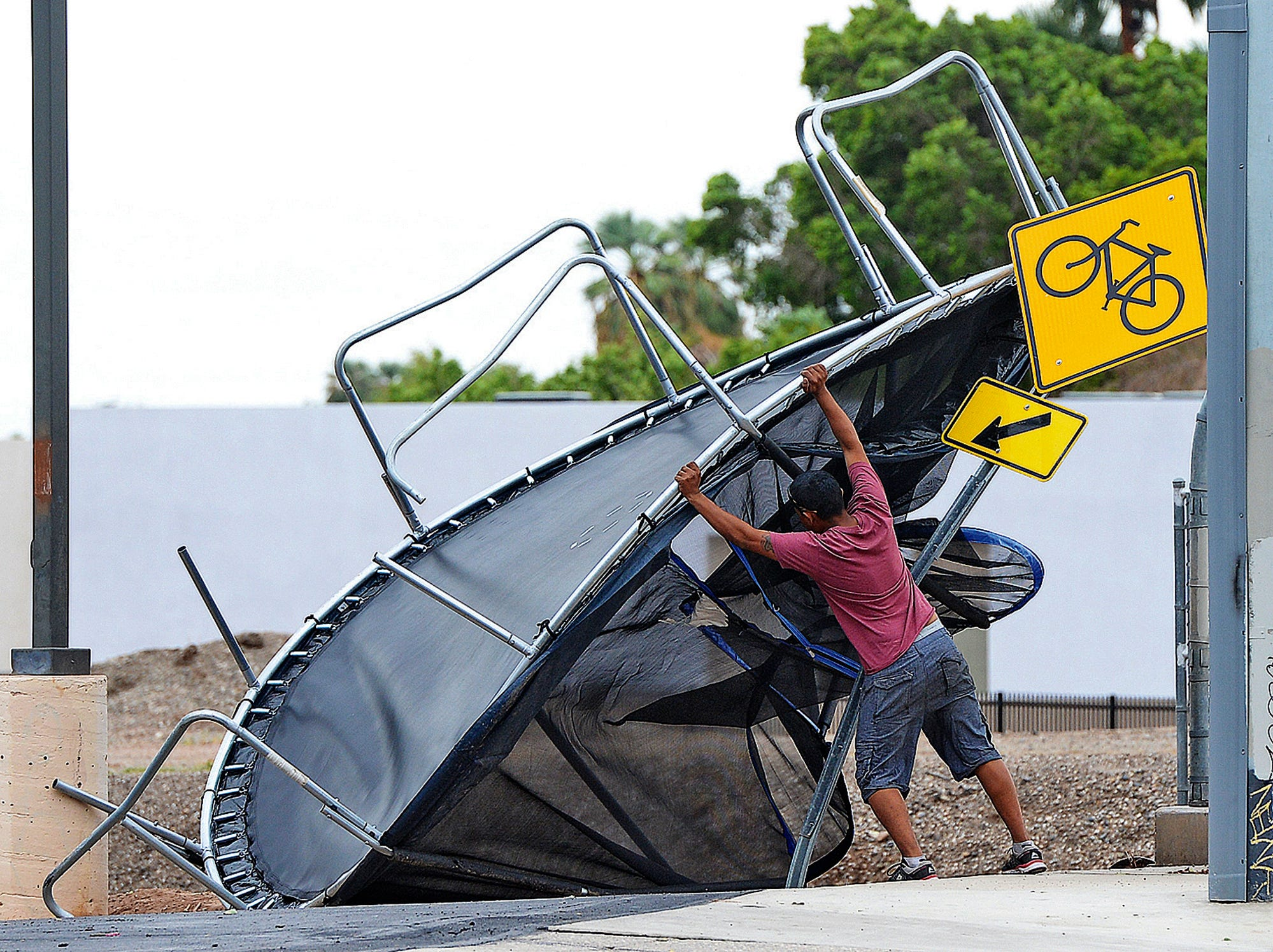 Joel Negrete begins moving a trampoline that was once in his yard before the start of Sunday's early afternoon rain storm.