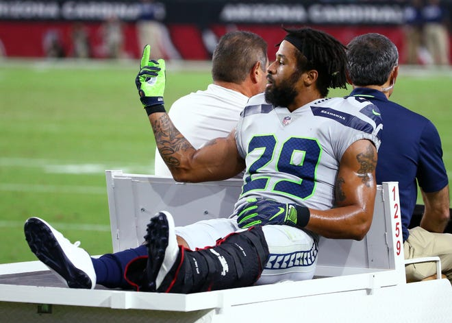 Seattle Seahawks safety Earl Thomas gestures towards his bench after breaking his lower left leg against the Arizona Cardinals in the second half at State Farm Stadium in Glendale, Ariz.