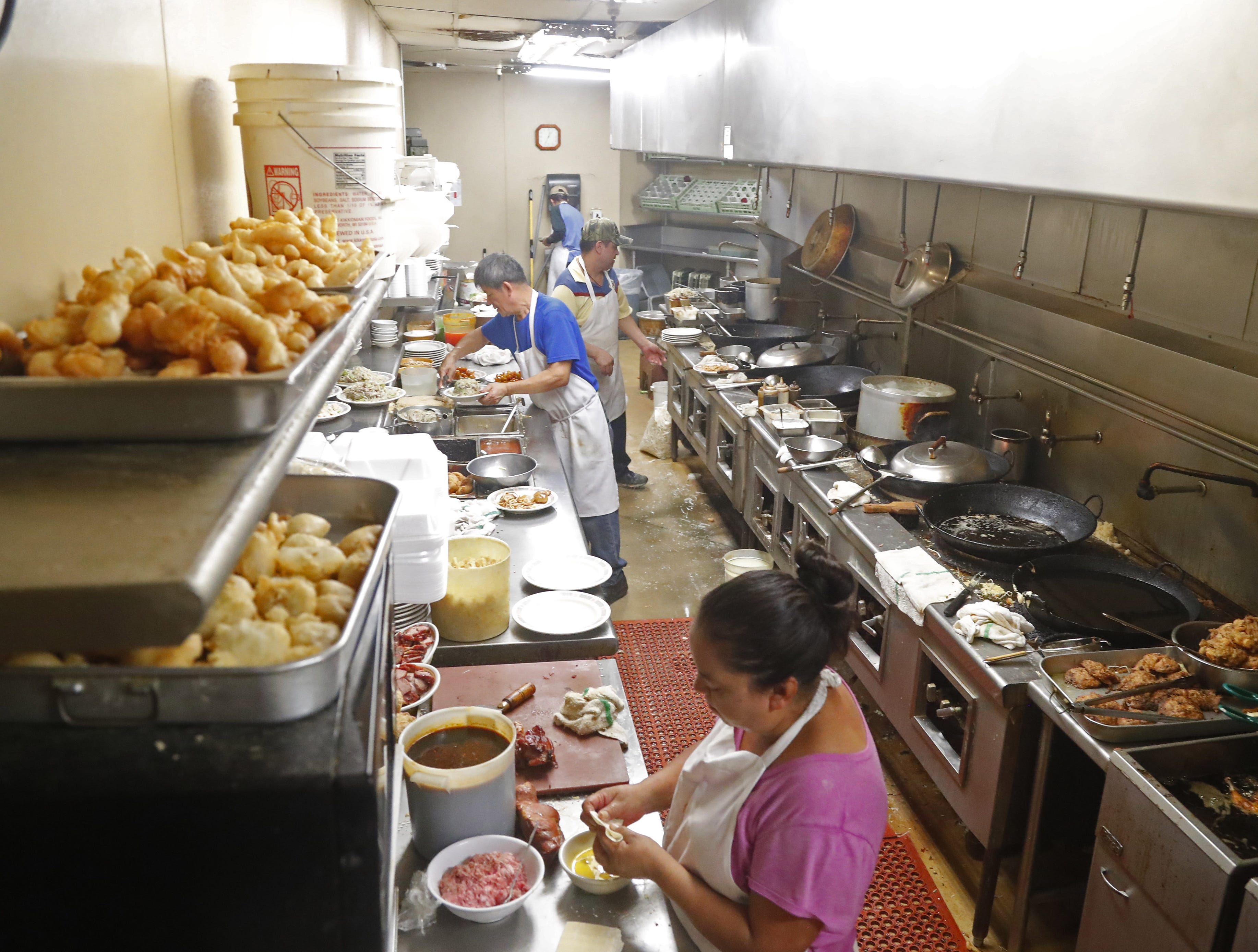 The kitchen cooks up orders on Sing High Chop Suey House's final day open in downtown Phoenix, Ariz. on Sept. 30, 2018.