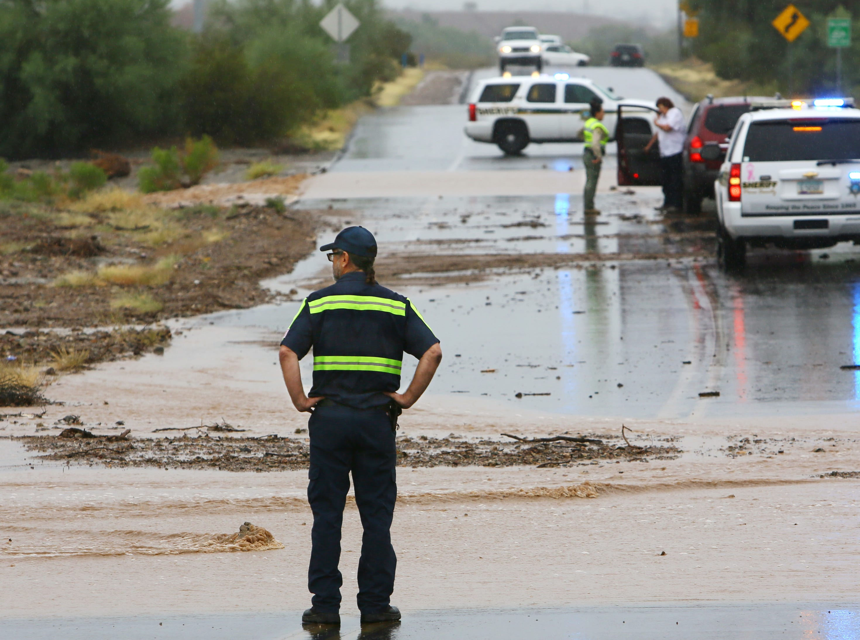 A tow truck driver eyes a flooded section of Silverbell Road at West Benjamen Road during rain from the remnants of Hurricane Rosa in Tucson on Oct. 1, 2018.