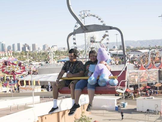 La familia disfruta de paseos y otras actividades divertidas en la Feria Estatal de Arizona el 12 de octubre de 2017.