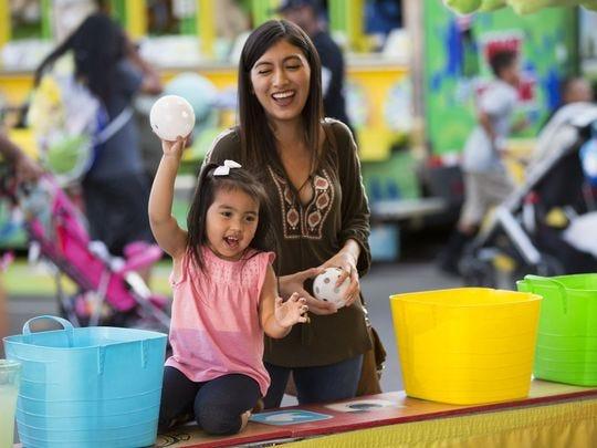 Summer Fernández, de 19 años, observa a su sobrina Jayde Fernández, de 3 años, lanzar una pelota en el Goblet Toss en la Feria Estatal de Arizona el 16 de octubre de 2016.