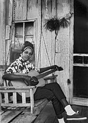 "Jessie Mae Hemphill tunes her guitar on her porch in this 1967 photograph by George Mitchell, part of the ""American Roots Music"" exhibit at the Howland Cultural Center in Beacon."