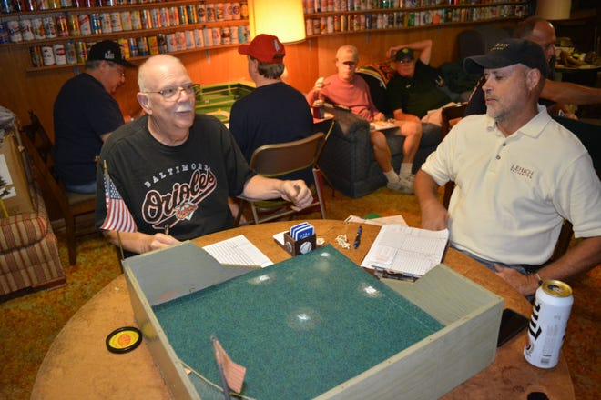 Dick Silar, left, and Dave Mann, right, play the APBA baseball board game. Silar started the local league in 1970.