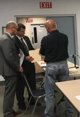 Attorney Anthony Bowser, far left, and Newberry Township solicitor Andrew Miller discuss Save Rite Auto case details with the township's zoning officer.