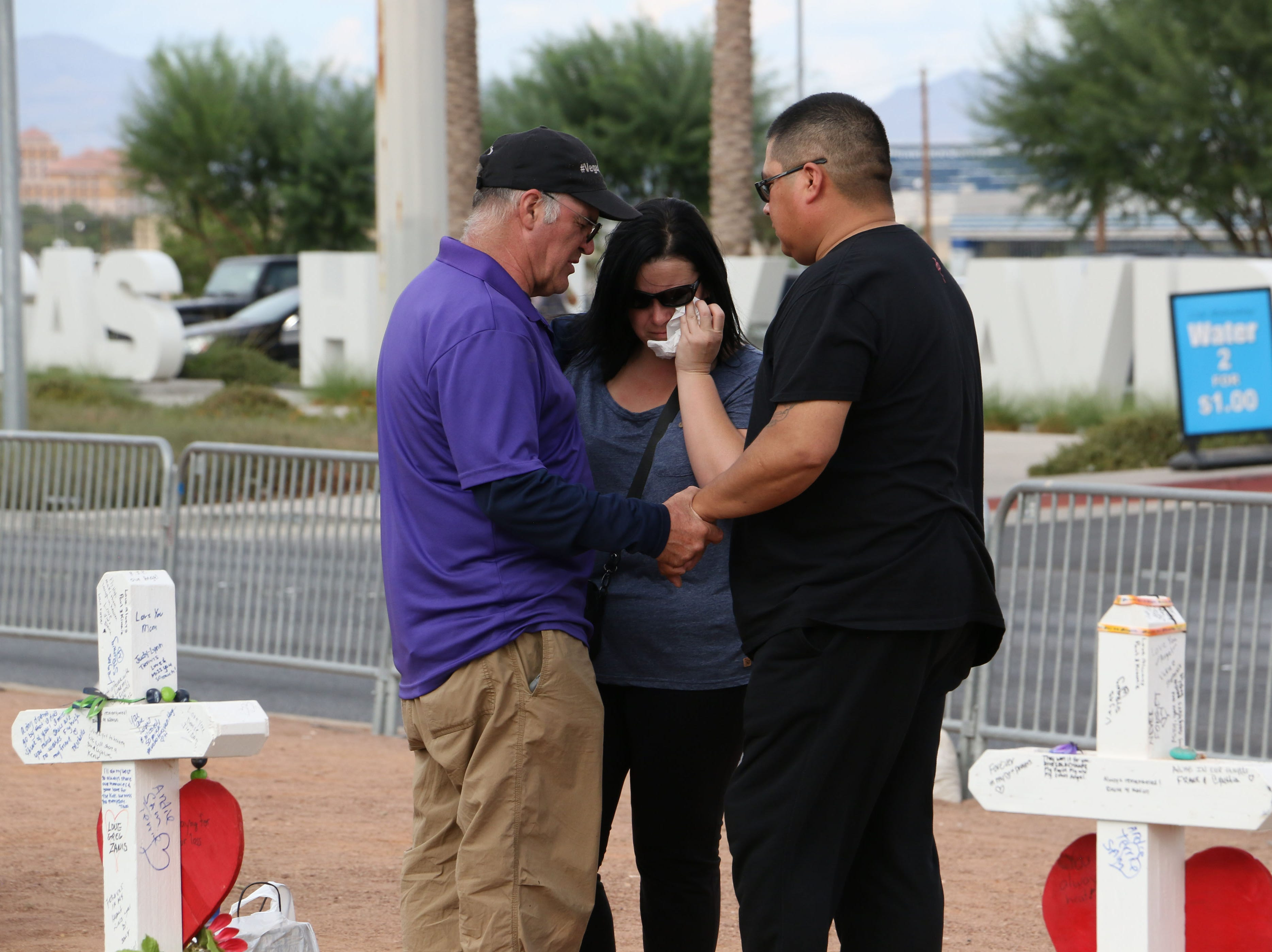 People pray together at a memorial set up next to the welcome to Las Vegas sign as Las Vegas remembers the mass shooting at the Route 91 Harvest Festival one year later on Oct. 1, 2018.