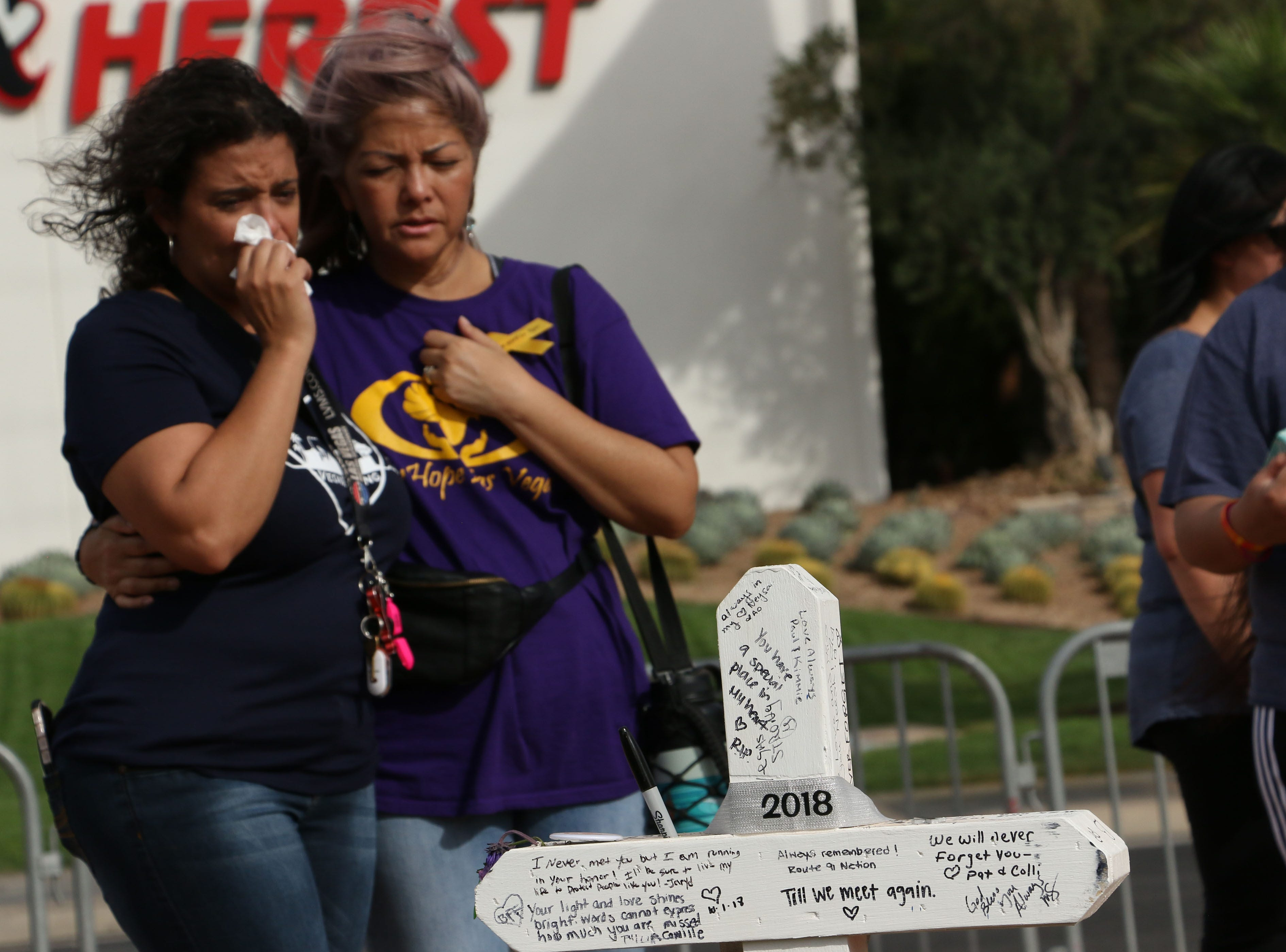 Triana Grigsby, left, and Allison Iha hold each other at a memorial set up next to the welcome to Las Vegas sign as Las Vegas remembers the mass shooting at the Route 91 Harvest Festival one year later on Oct. 1, 2018.