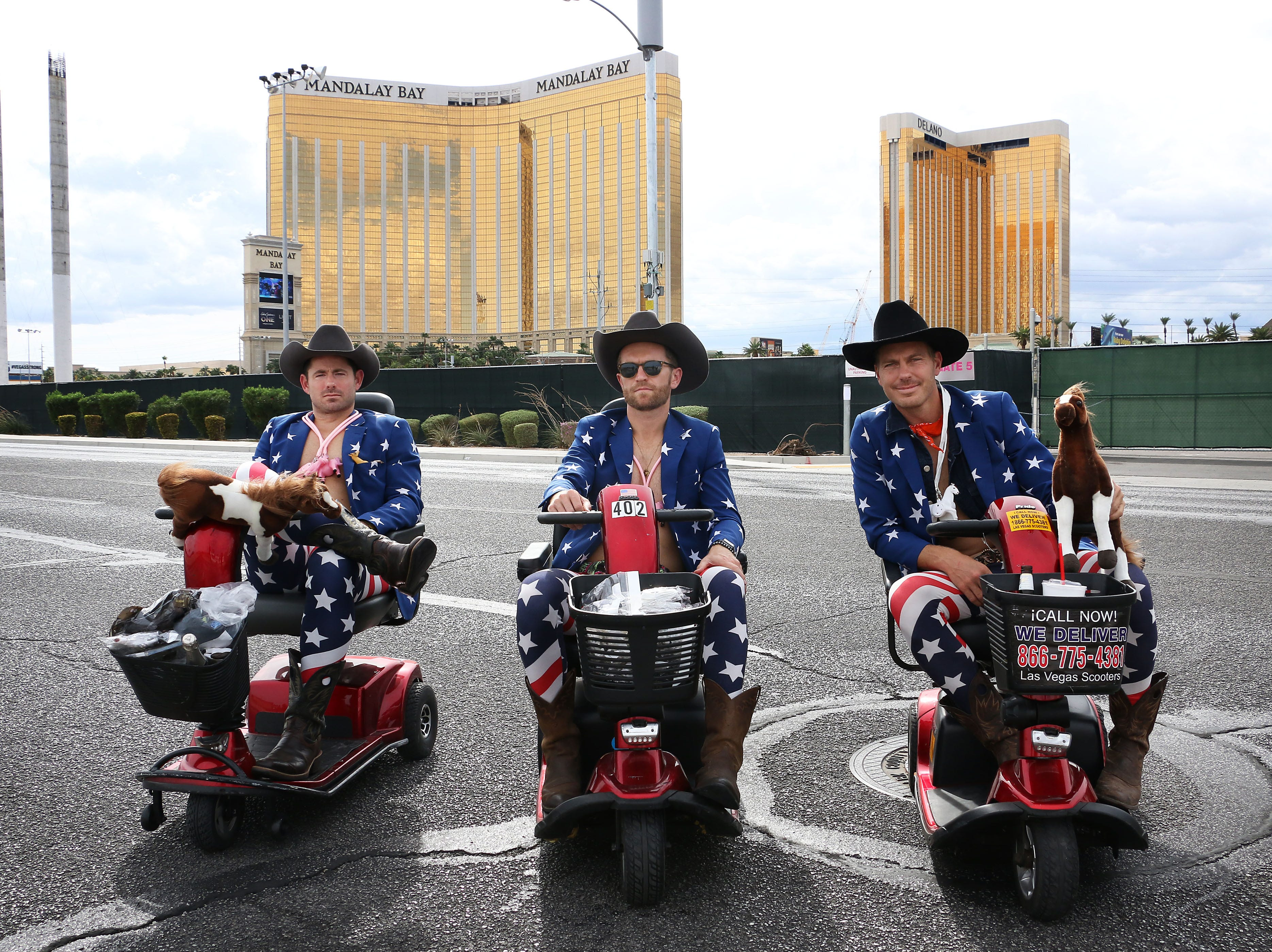 From left, survivors Josh Zeyak, Dylan Mason and Leo Van Warmerdam pose for a portrait in front of the Route 91 Harvest Festival concert grounds as Las Vegas remembers the mass shooting one year later on Oct. 1, 2018.  The three men are wearing exactly the same outfits they wore to the festival one year ago. The FBI recovered their jackets for them.  They also rode scooters, for fun, to the festival.