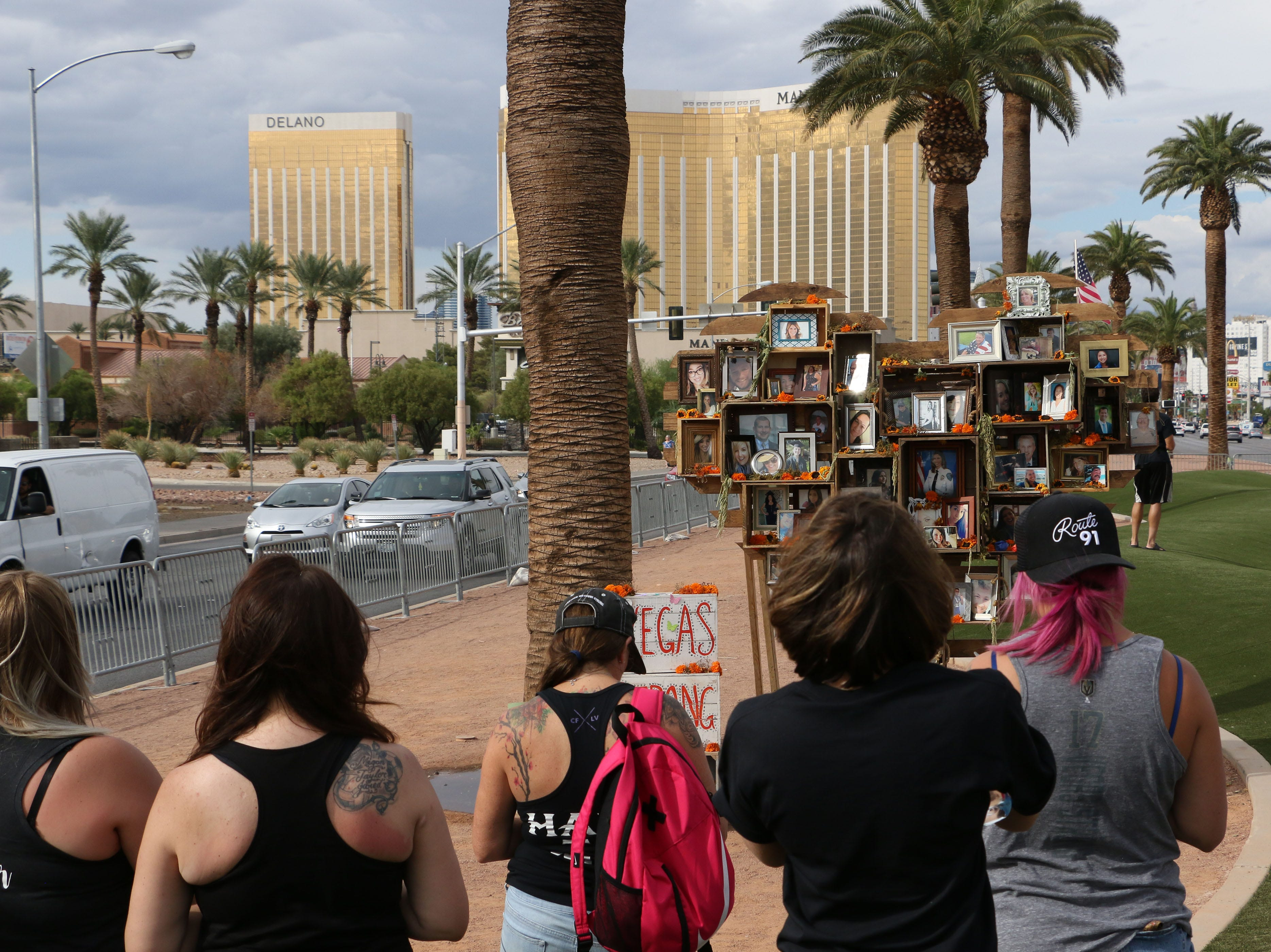 People gather at a memorial set up next to the welcome to Las Vegas sign as Las Vegas remembers the mass shooting at the Route 91 Harvest Festival one year later on Oct. 1, 2018.