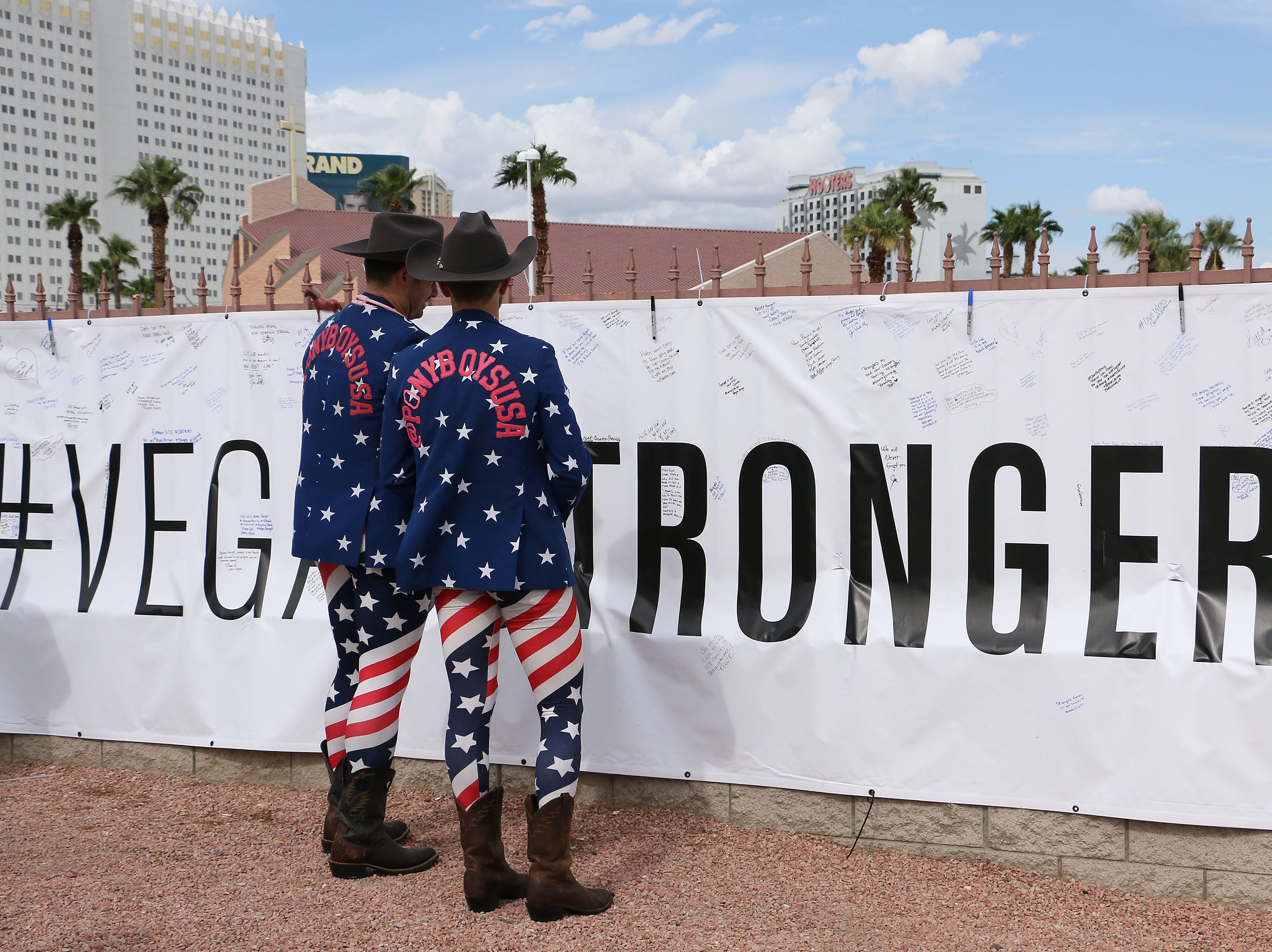 Leo Van Warmerdam, left, and Dylan Mason read messages on a sign near the Route 91 Harvest Festival concert grounds as Las Vegas remembers the mass shooting one year later on Oct. 1, 2018.  The two men are wearing exactly the same outfits they wore to the festival one year ago. The FBI recovered their jackets for them.