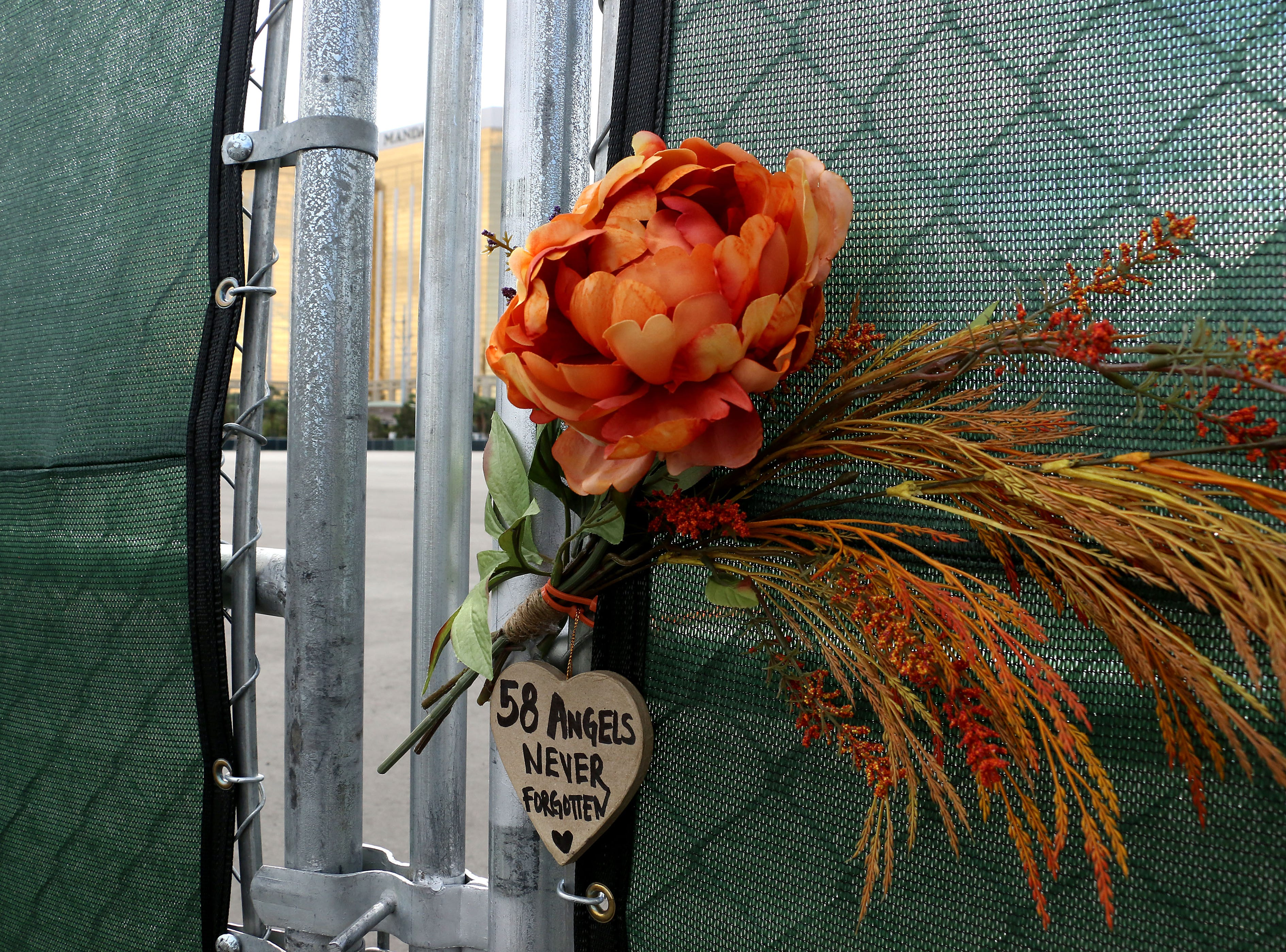 A flower and sign adorn the fence to the Route 91 Harvest Festival concert grounds next to the Mandalay Bay as Las Vegas remembers the mass shooting one year later on Oct. 1, 2018.