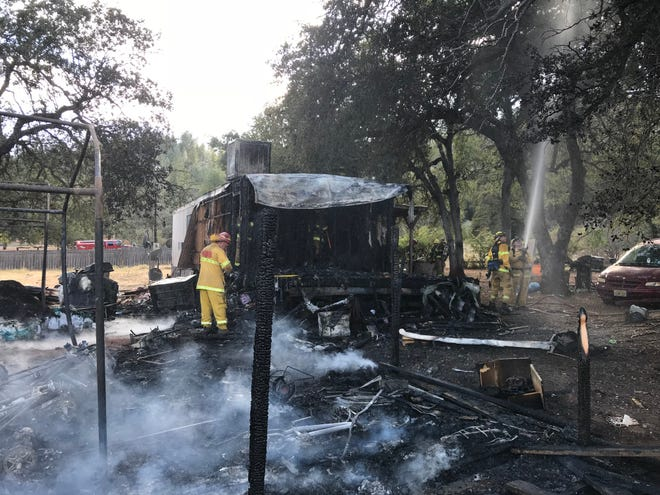 Fire destroyed a mobile home and two outbuildings Sunday.