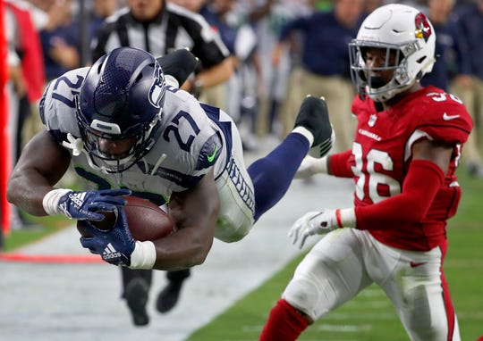 Seattle Seahawks running back Mike Davis (27) dives in for a touchdown as Arizona Cardinals defensive back Budda Baker (36) defends during the first half of an NFL football game, Sunday, Sept. 30, 2018, in Glendale, Ariz. (AP Photo/Rick Scuteri)