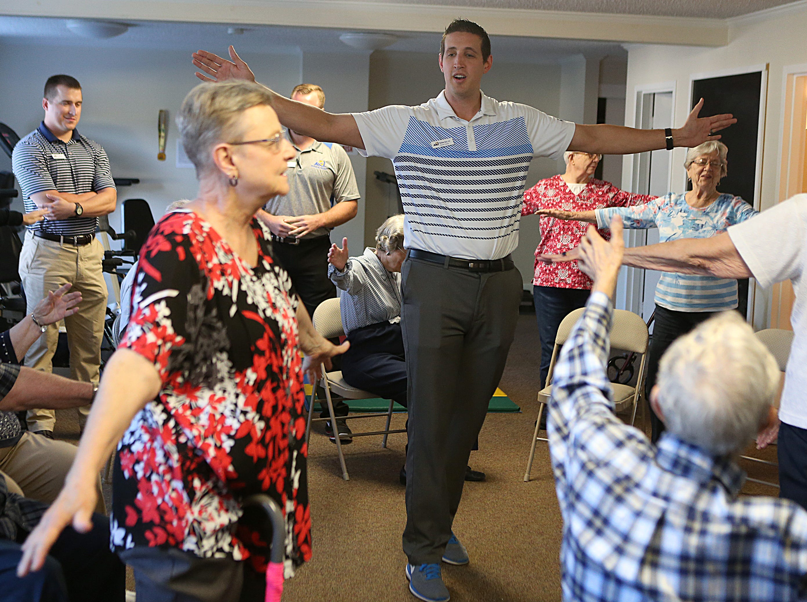 Matt Ricci, a physical therapy student at Angelo State University, does arm exercises with residents during a Balance and Fall Risk Reduction Program for seniors at Baptist Retirement Community Monday, Oct. 1, 2018.
