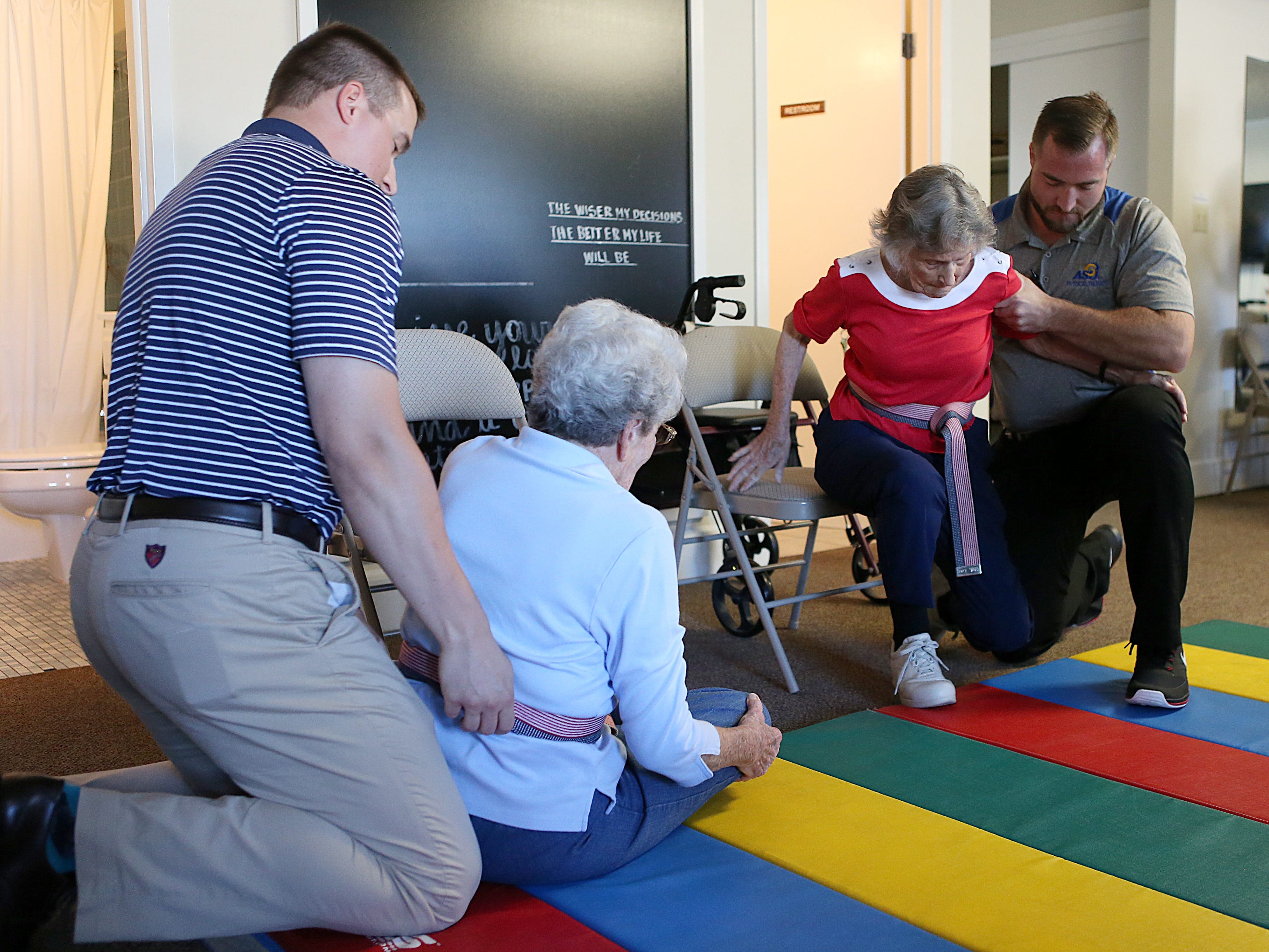Residents June Heck (left) and Barbara Marshal are helped onto a mat  by Tyler Althof (left) and Dane Grimes, physical therapy students from Angelo State University down during a a Balance and Fall Risk Reduction Program for seniors at Baptist Retirement Community Monday, Oct. 1, 2018.