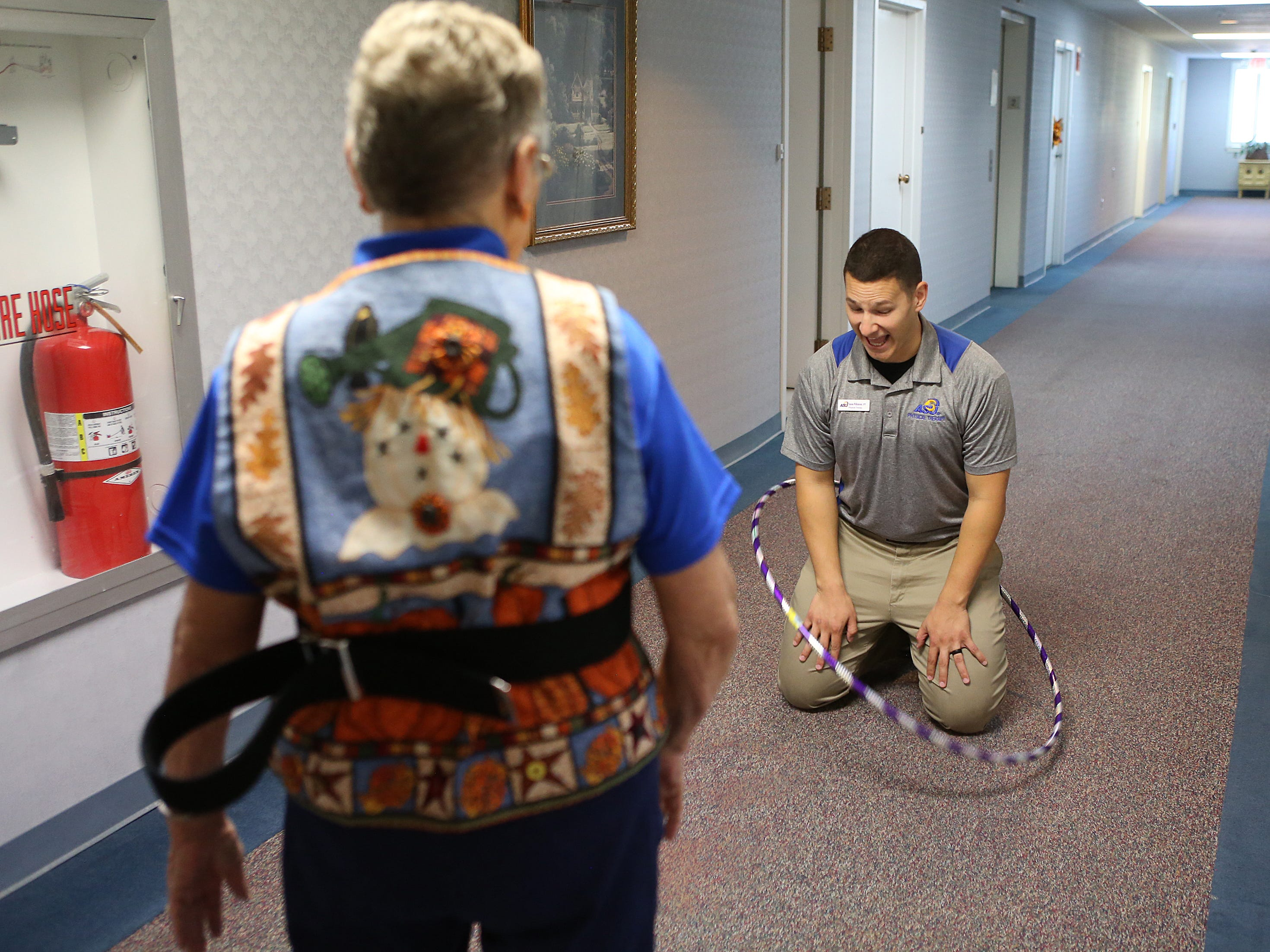 Angelo State University physical therapy student Jason Wilkinson laughs as resident Virginia Lane tosses a hula hoop around him during a Balance and Fall Risk Reduction Program for seniors at Baptist Retirement Community Monday, Oct. 1, 2018.
