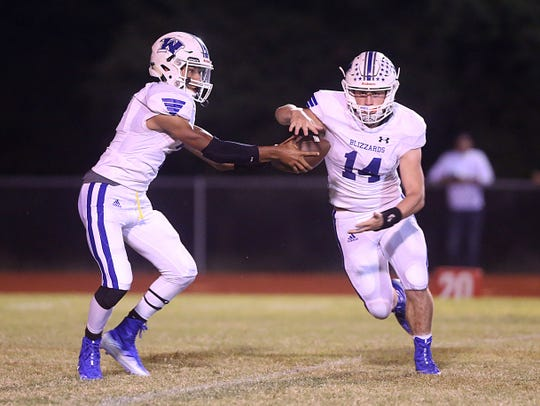 Winters' Nick Brown (#14) takes the ball from teammate Jovan Young (#7) during Friday nights game in Chistoval, Sept. 28, 2018.