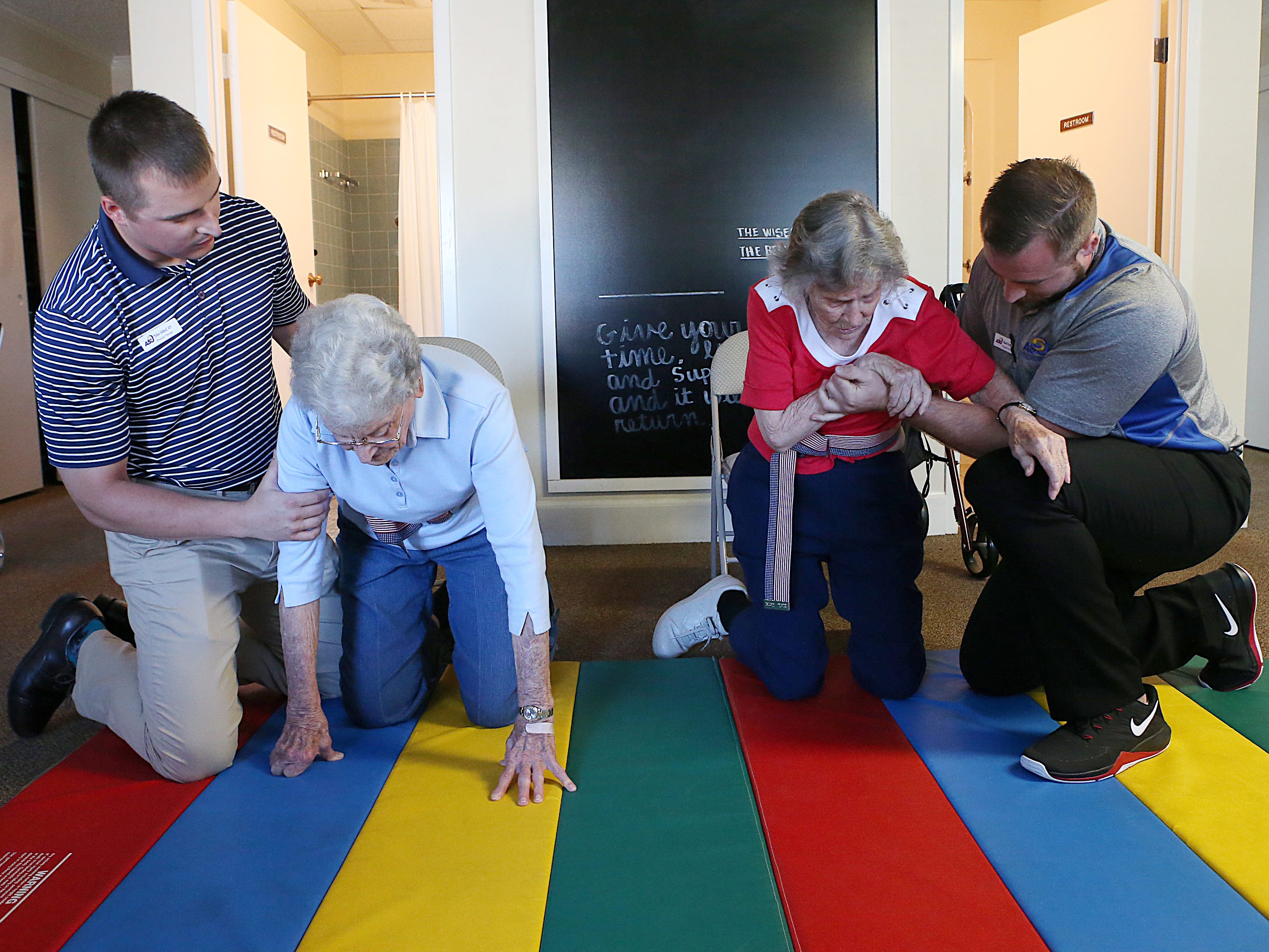 Residents June Heck (left) and Barbara Marshal are helped onto a mat  by Tyler Althof (left) and Dan Grimes, physical therapy students from Angelo State University down during a Balance and Fall Risk Reduction Program for seniors at Baptist Retirement Community Monday, Oct. 1, 2018.