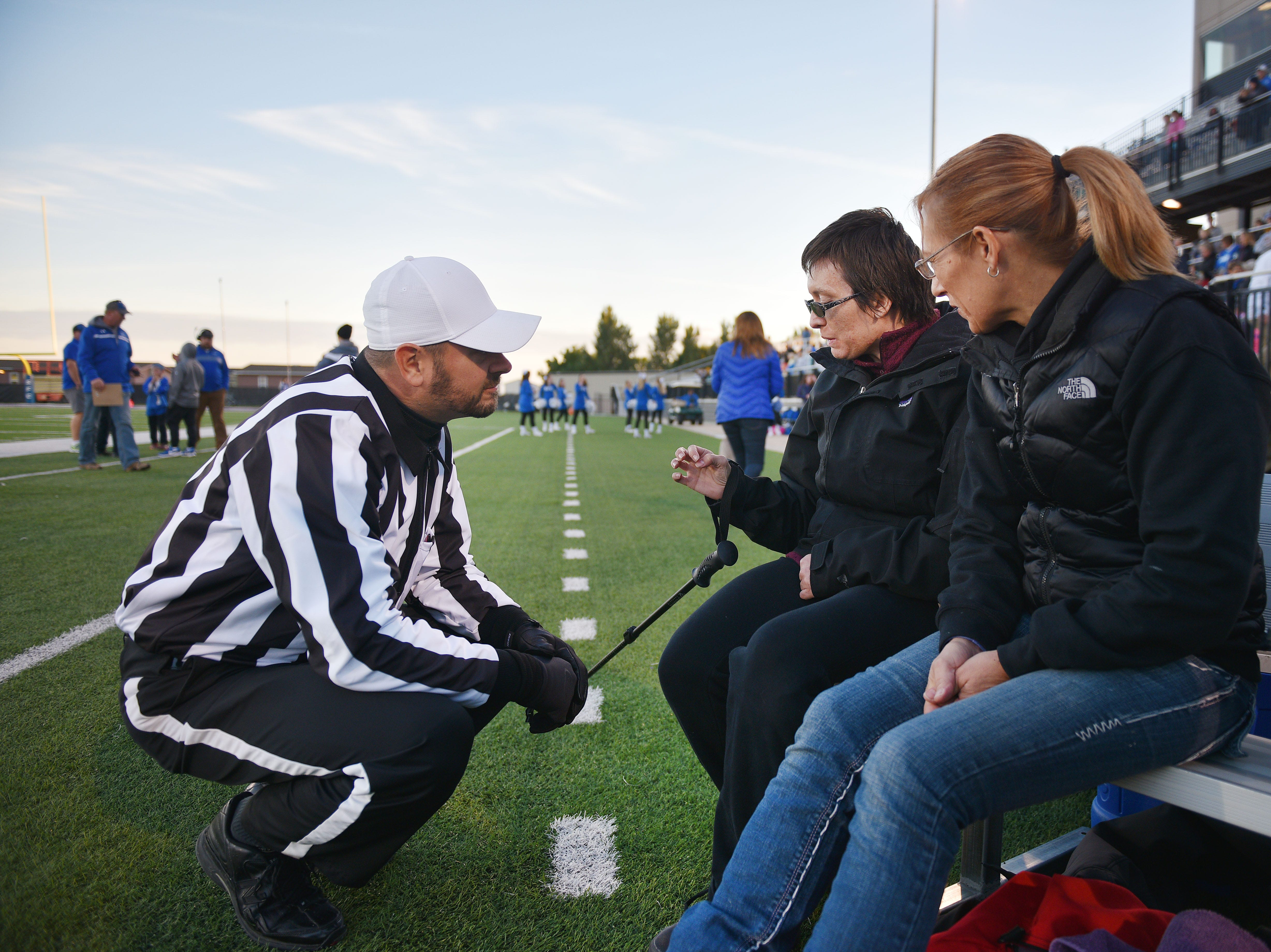 Referee Micheal Fuller gives Ashley Van Hemert instructions for the coin toss before the Sioux Falls Christian game, Friday Sept. 28, at Bob Young Field University Of Sioux Falls Stadium.
