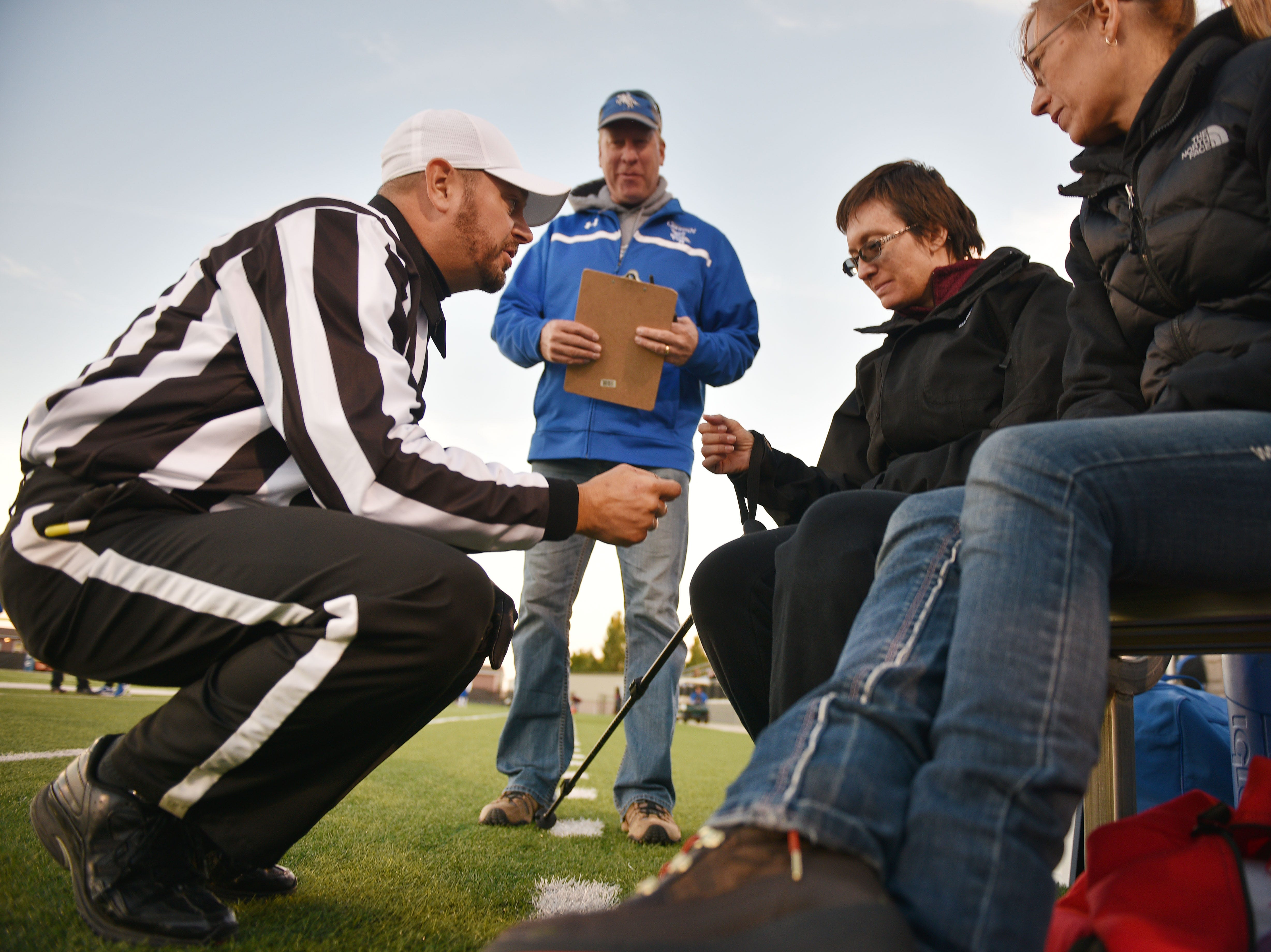 Referee Micheal Fuller and athletic director Jim Groen give Ashley Van Hemert instructions for the coin toss before the Sioux Falls Christian game, Friday Sept. 28, at Bob Young Field University Of Sioux Falls Stadium.